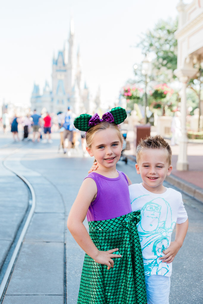 Little girl in purple and green mermaid dress with mermaid Mickey ears with little boy in Buzz Lightyear t-shirt in front of the castle in Magic Kingdom at Disney World.