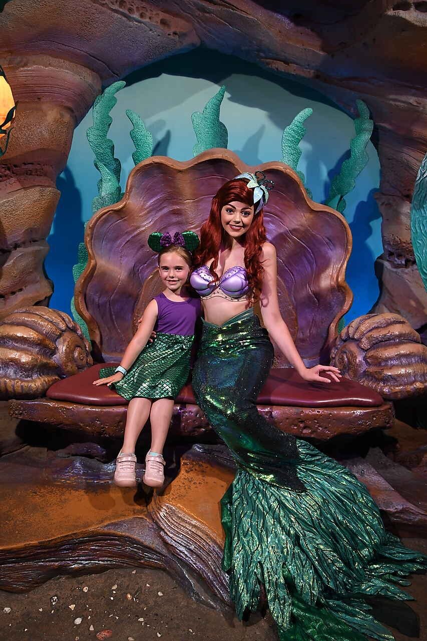 Little girl dressed in a purple and green mermaid dress and matching Mickey ears sitting with Ariel in a clam shell at Disney World.
