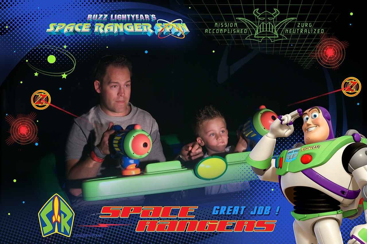 Dad and son concentrating on shooting their lasers on Buzz Lightyear's Space Ranger Spin.