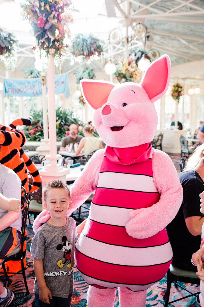 Little boy in a Mickey Mouse t-shirt with Piglet at Crystal Palace restaurant at Magic Kingdom in Disney World.