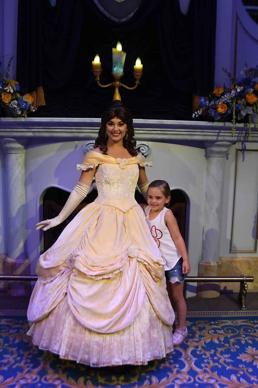 Little girl posing with Belle in the Beast's Library at Enchanted Tales with Belle.