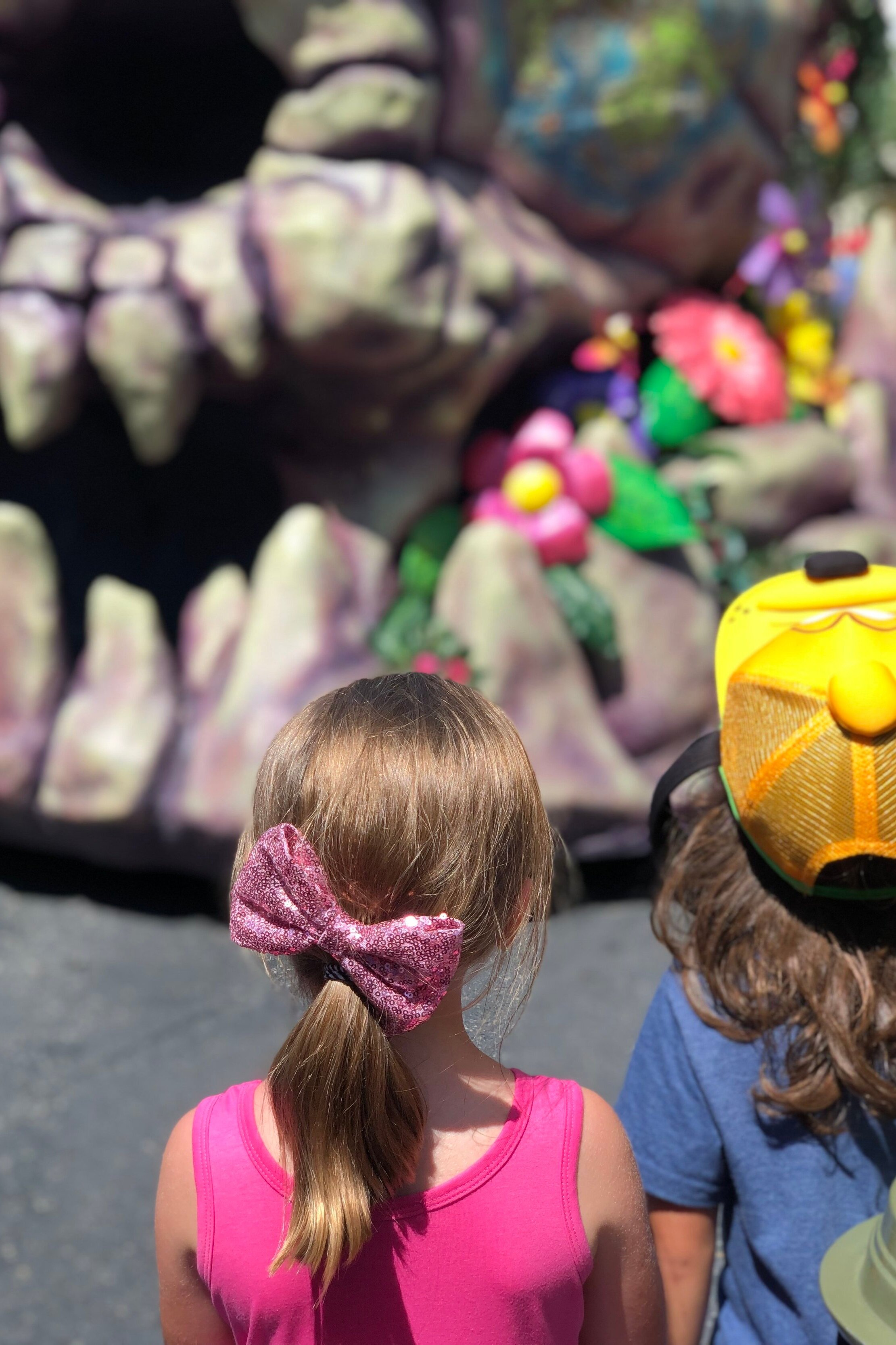 Back of little girl and little boy's head while watching the parade at Magic Kingdom Disney World.