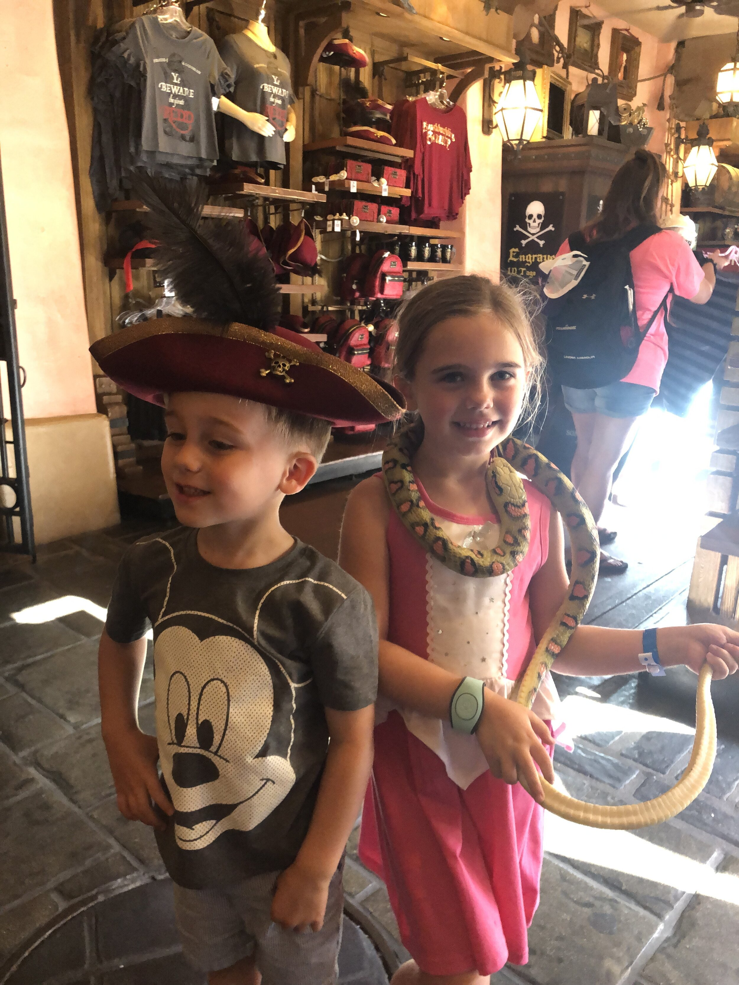 Little kids trying on pirate hats and playing with rubber snakes at the Pirates of the Caribbean shop in Magic Kingdom.