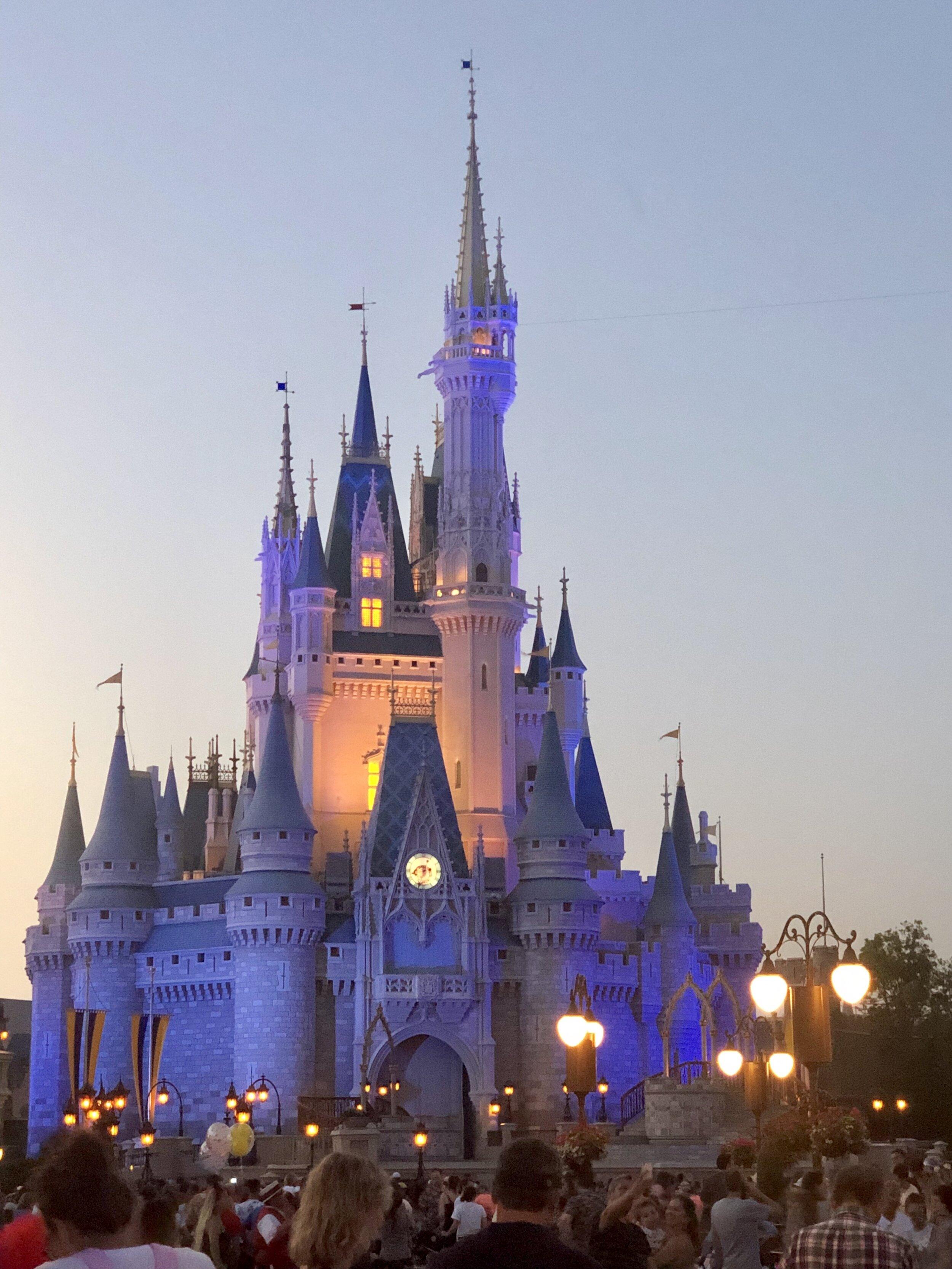Cinderella's castle lit up at twilight in Magic Kingdom Disney World.