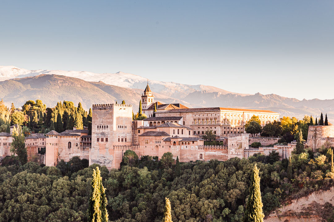 Sunset view of the entire Alhambra complex with snowcapped Sierra Nevada mountains in the background.
