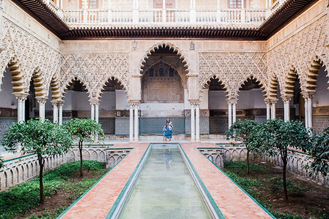 Interior of the Maidens Courtyard at the Alcazar in Seville with reflecting pond in the middle and ornately carved archways surrounding it.