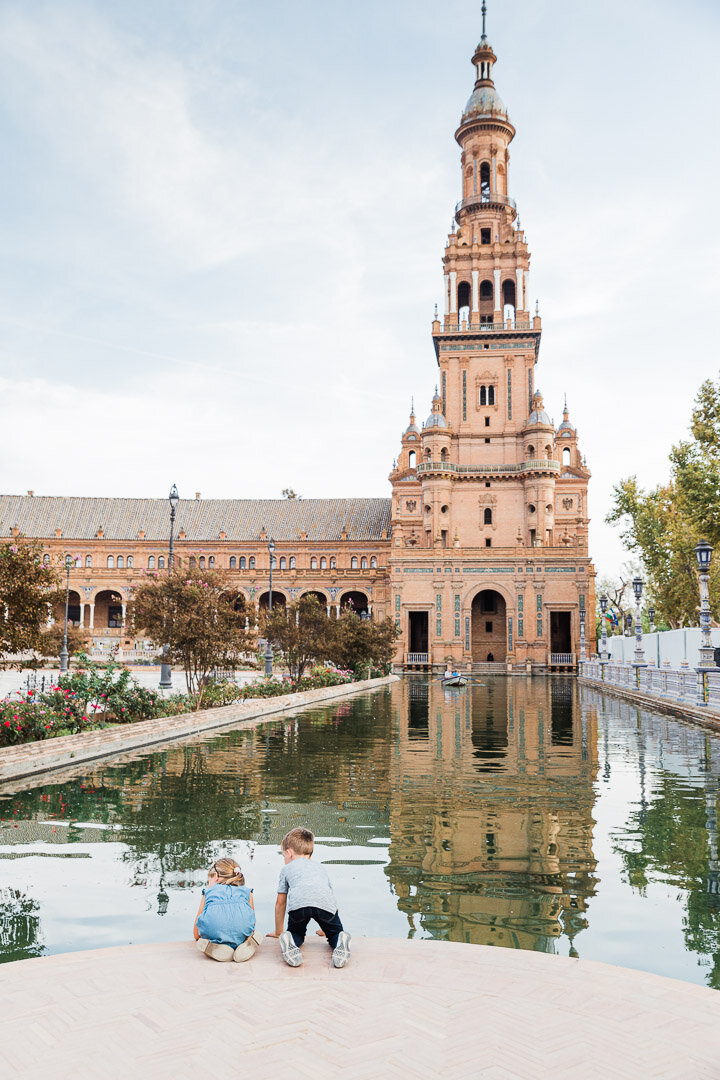 Kids kneeling down to look for fish in the canals of the Plaza de España in Seville, Spain.