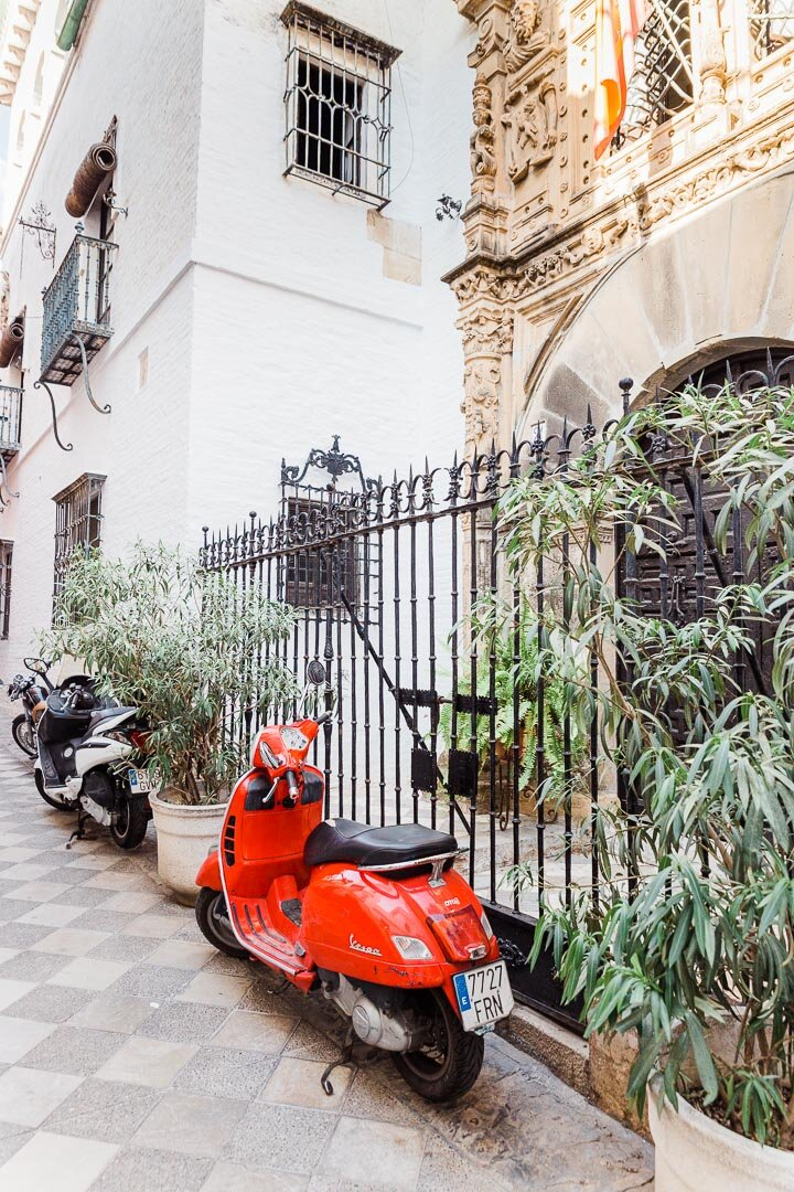 Red Vespa outside an iron gate in an alley in Seville, Spain.