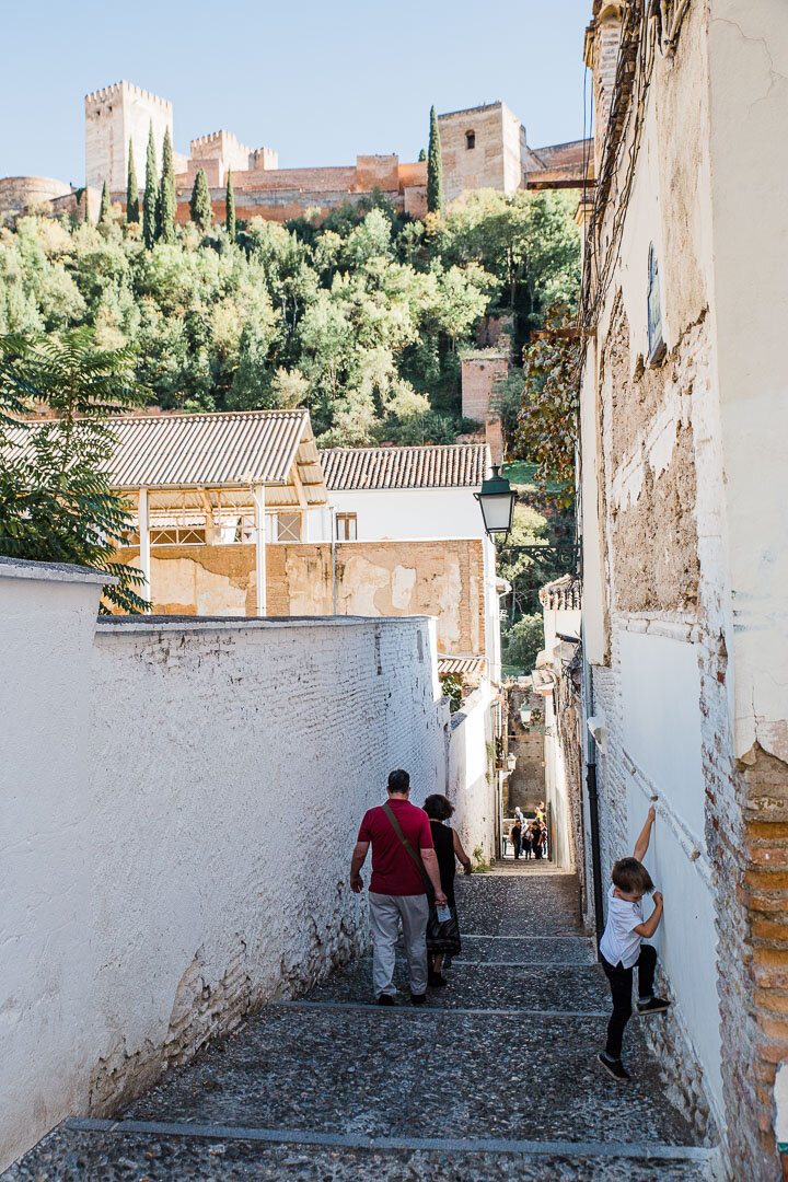 Narrow alley of the Albaicin neighborhood with the Alhambra palace above.