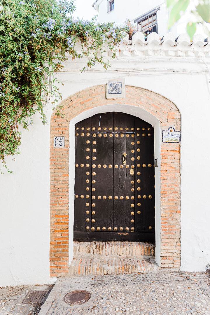 Dark wooden door adorned with brass circles set in a white wall in the Albaicin neighborhood in Granada.