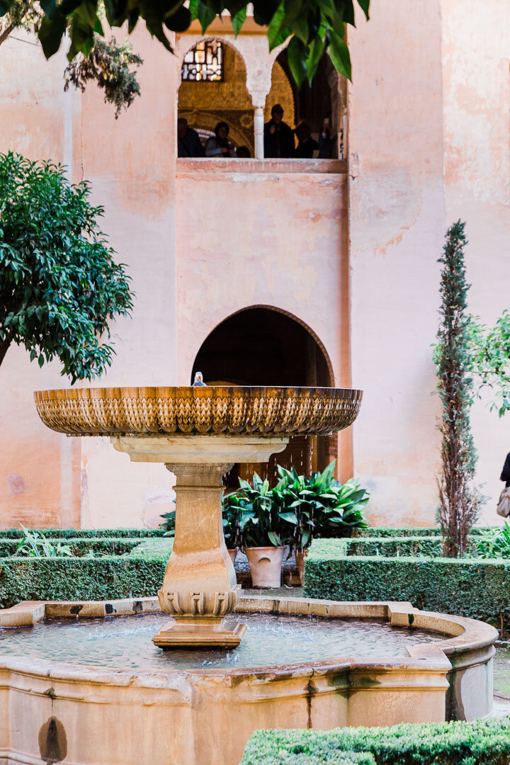 Fountain inside a pink courtyard of the Alhambra palace in Granada, Spain.