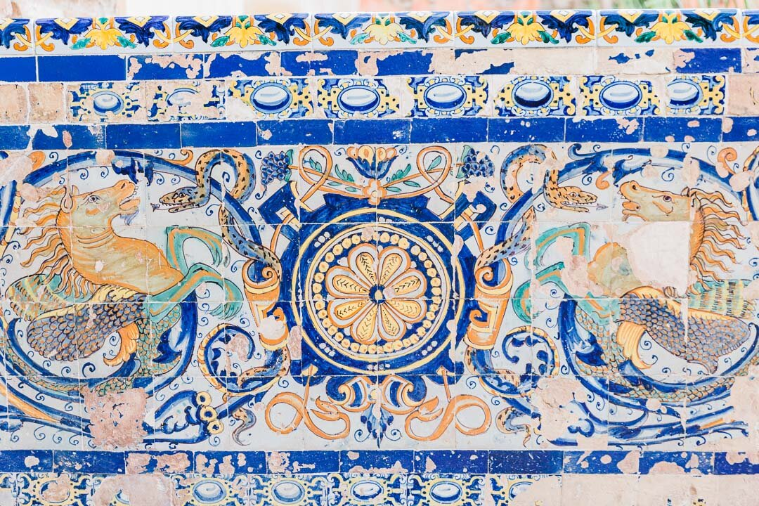 Painted tile work depicting snakes and horses, some of the tiles chipped and damaged, at Reál Alcazar in Seville, Spain.