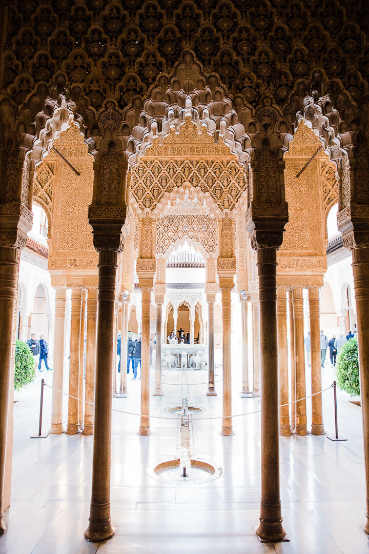 Lion courtyard and fountain through the intricately carved archways at the Alhambra palace in Granada, Spain.