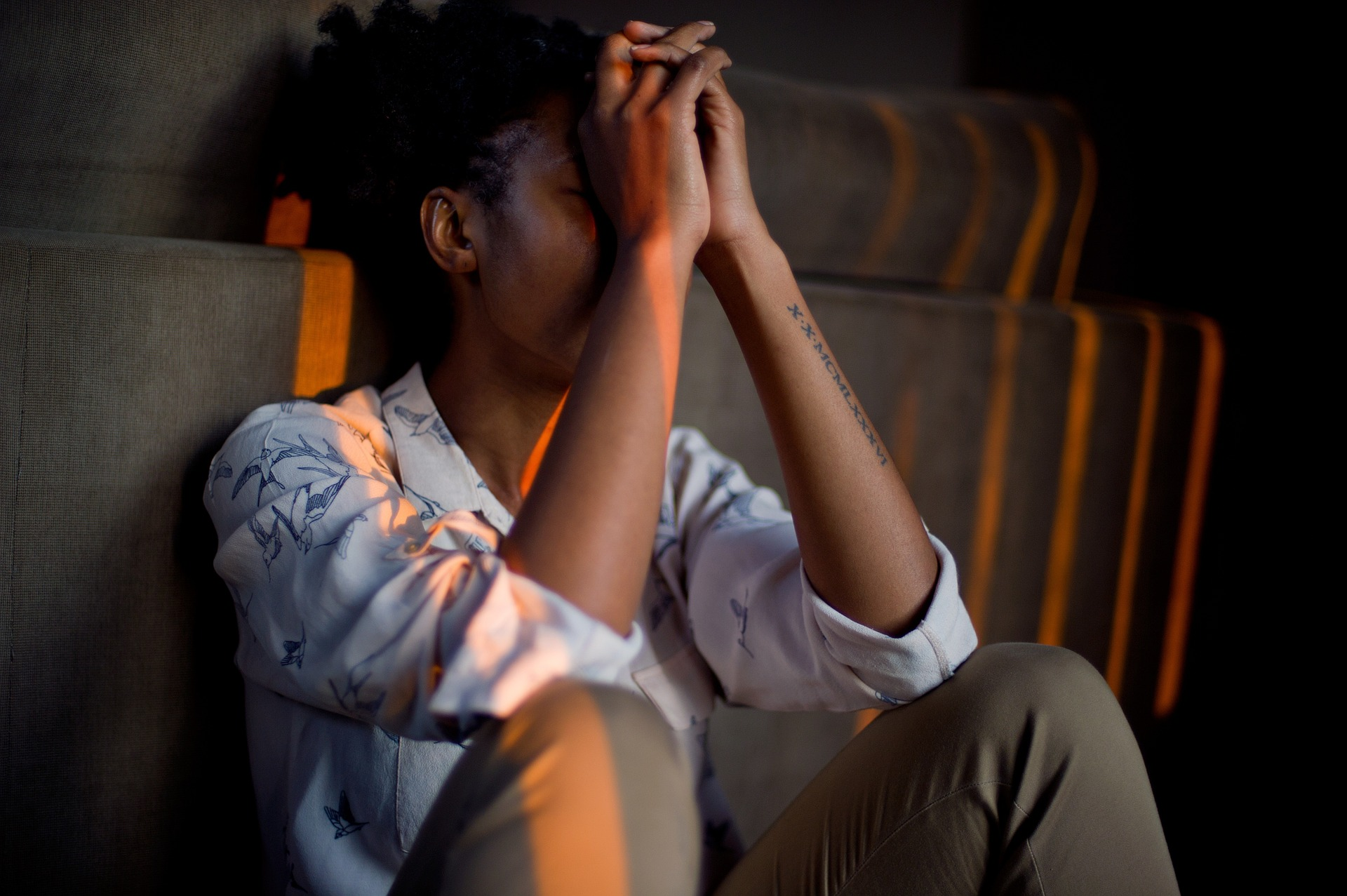 A younger Afro-Caribbean woman sitting with her head in her hands looking in pain.