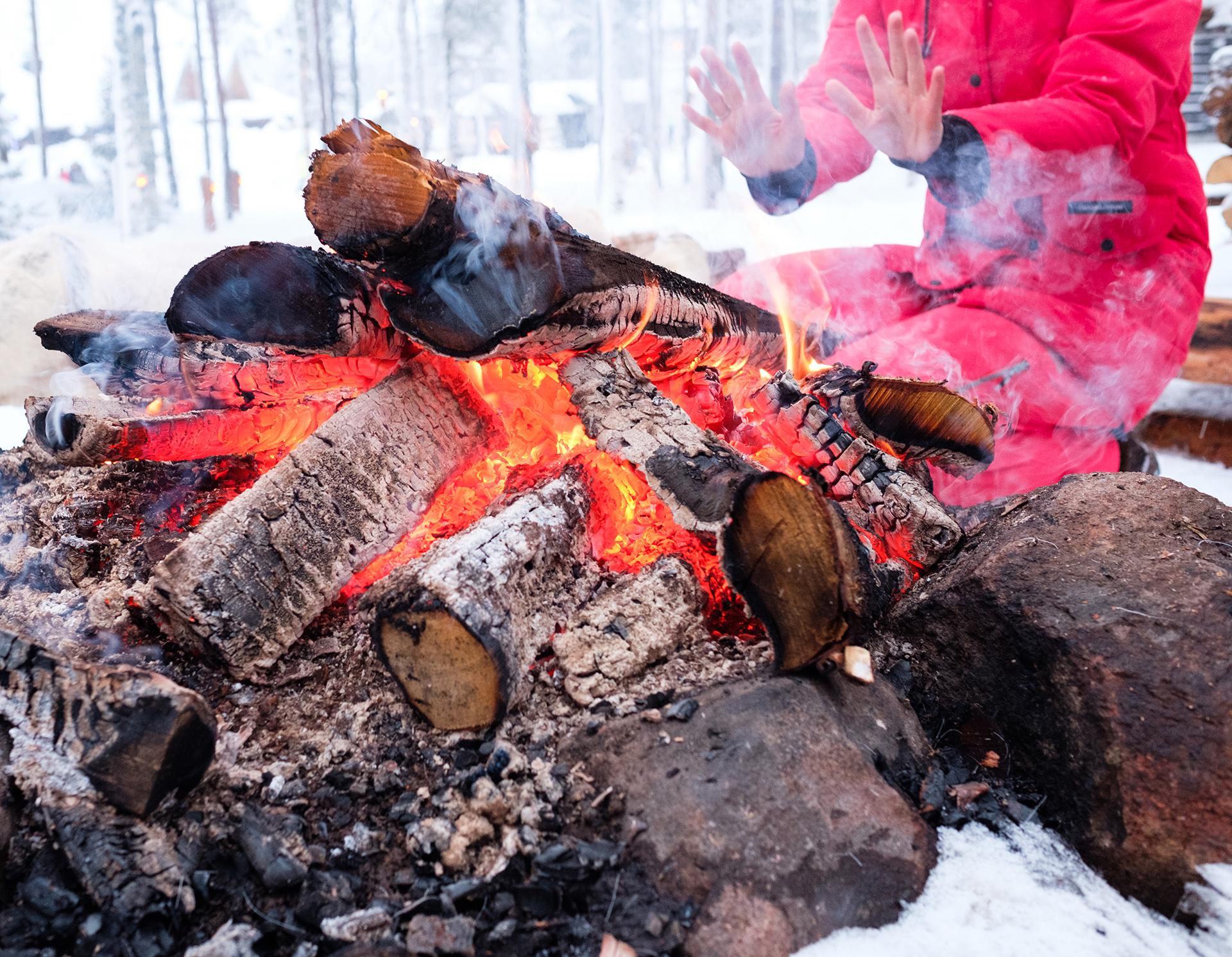 woman-near-bonfire-in-winter-landscape-P8GUDNX.jpg