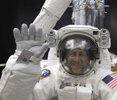 NASA Astronaut Michael Massimino waves at the camera during a spacewalk. Photo Courtesy NASA.GOV