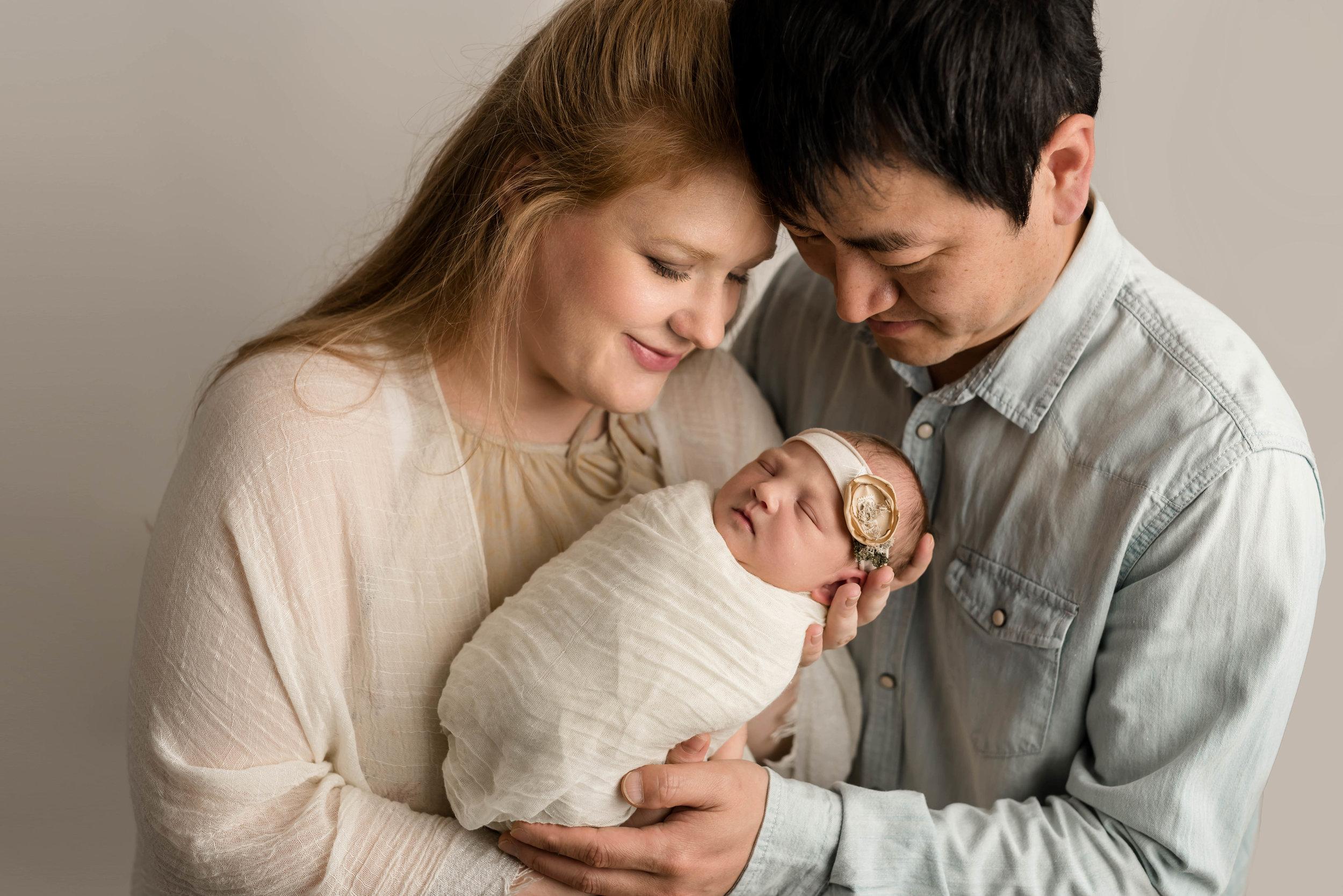 korean american family loving on their new baby girl at junebug photography studio in manhattan, kansas