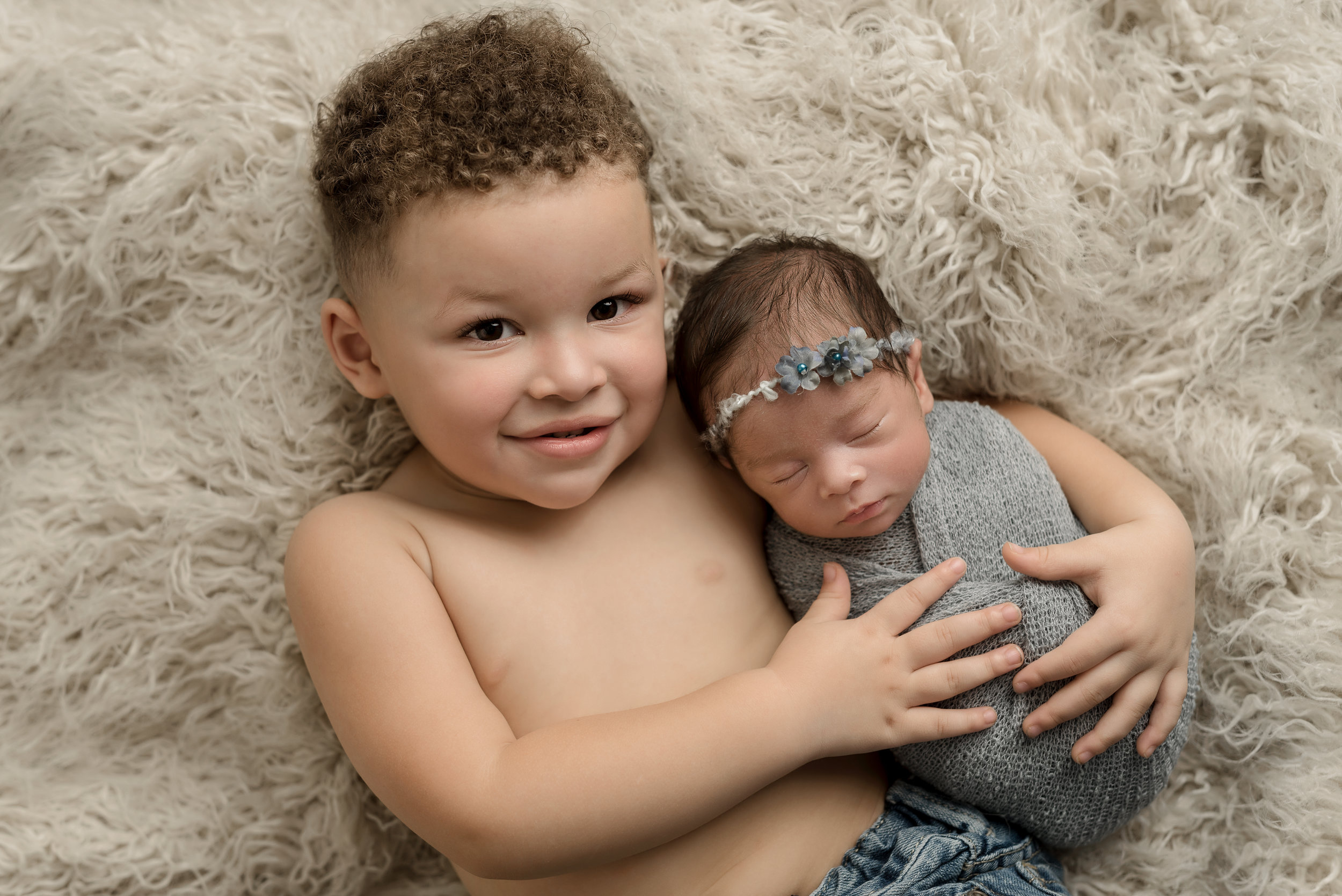 big brother loving his new baby sister at junebug photography studio in manhattan, ks