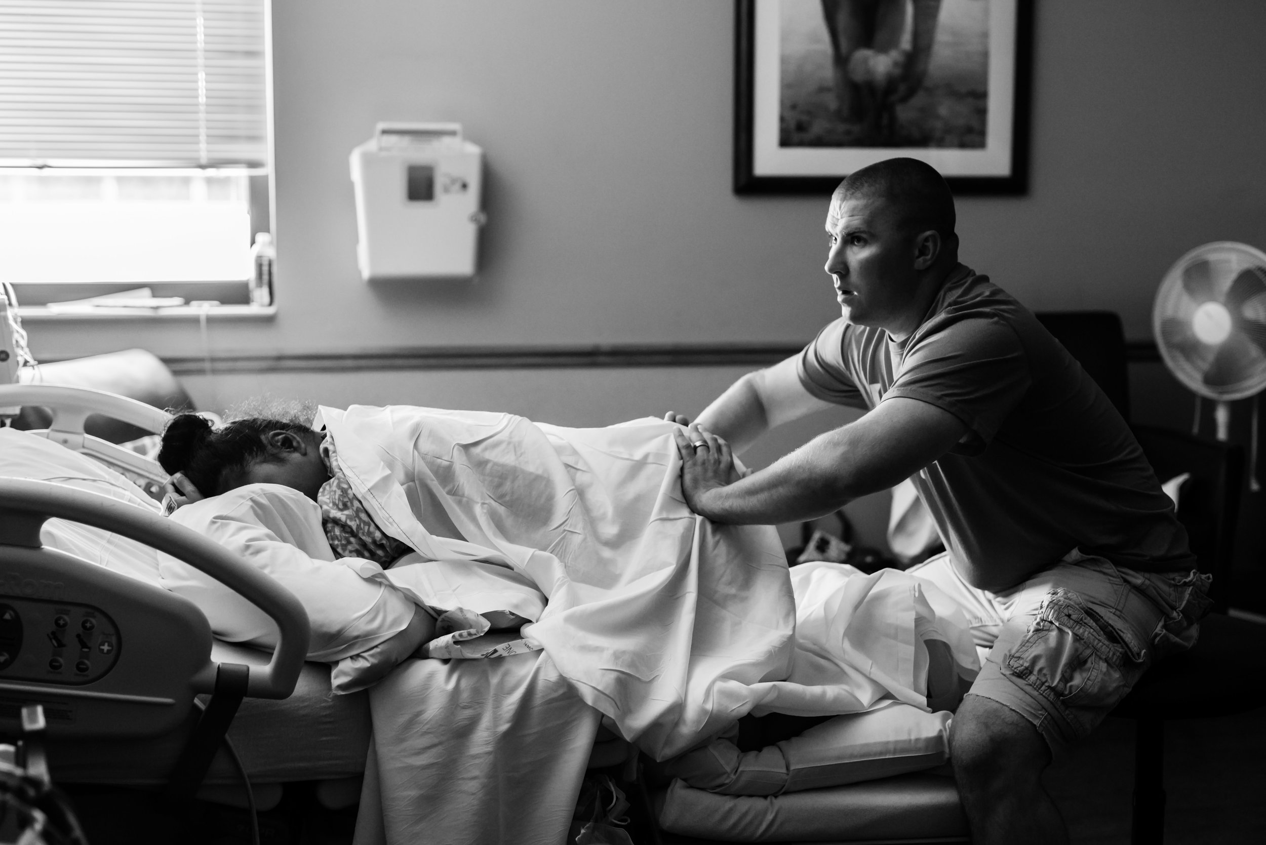 dad applying counter pressure for mom's back labor at a hospital birth with junebug photography studio in manhattan, kansas
