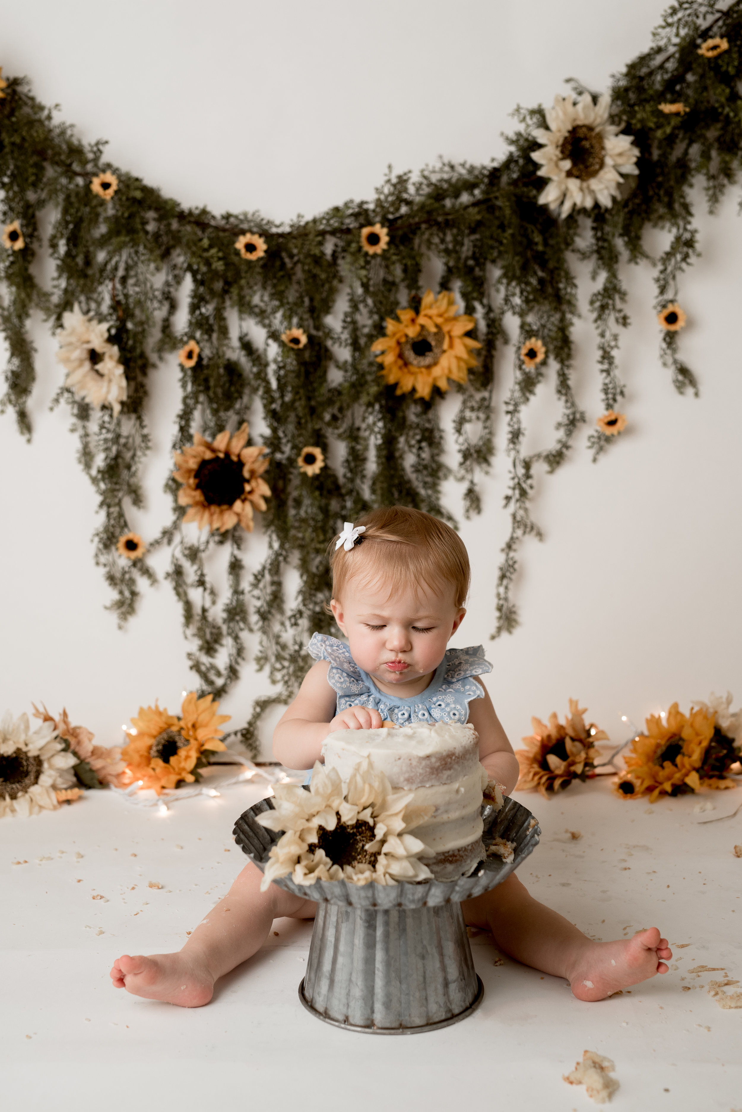 baby girl with a sunflower theme for her first birthday with junebug photography studio in manhattan, ks