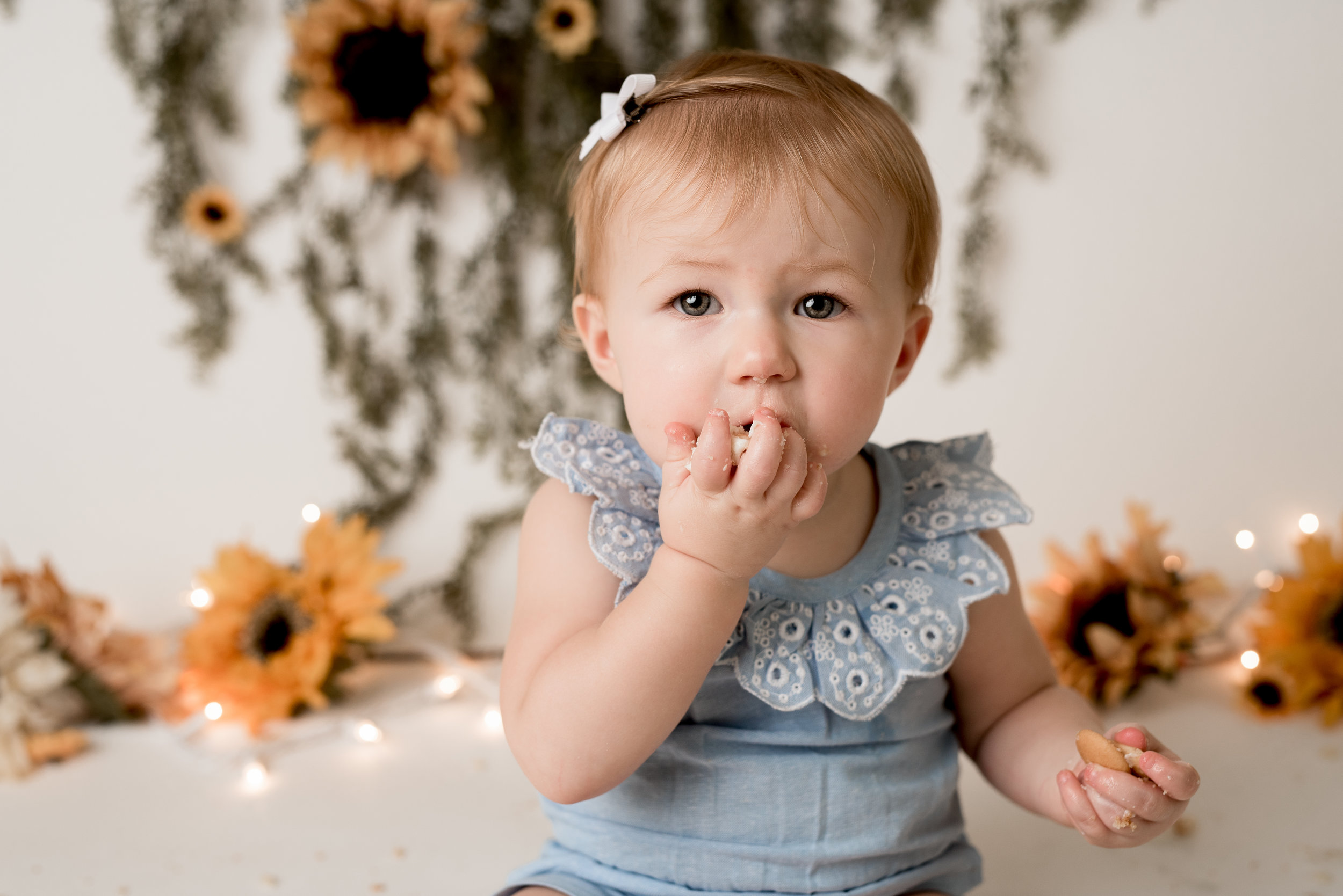 sunflower theme little girl eating her cake by the handful with junebug photography studio in manhattan, ks