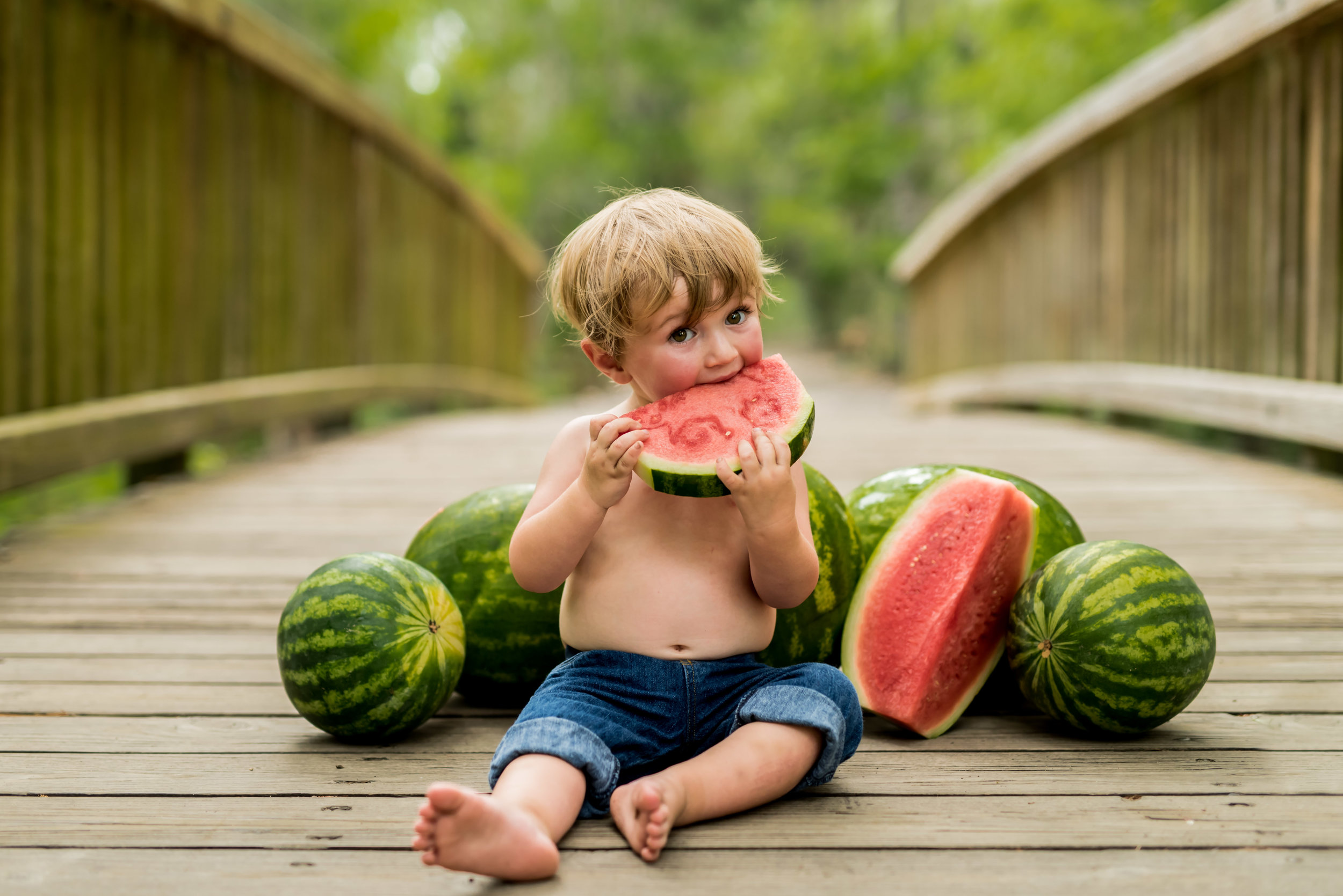 18 month old little boy eating watermelon in the summer with junebug photography studio in manhattan, ks