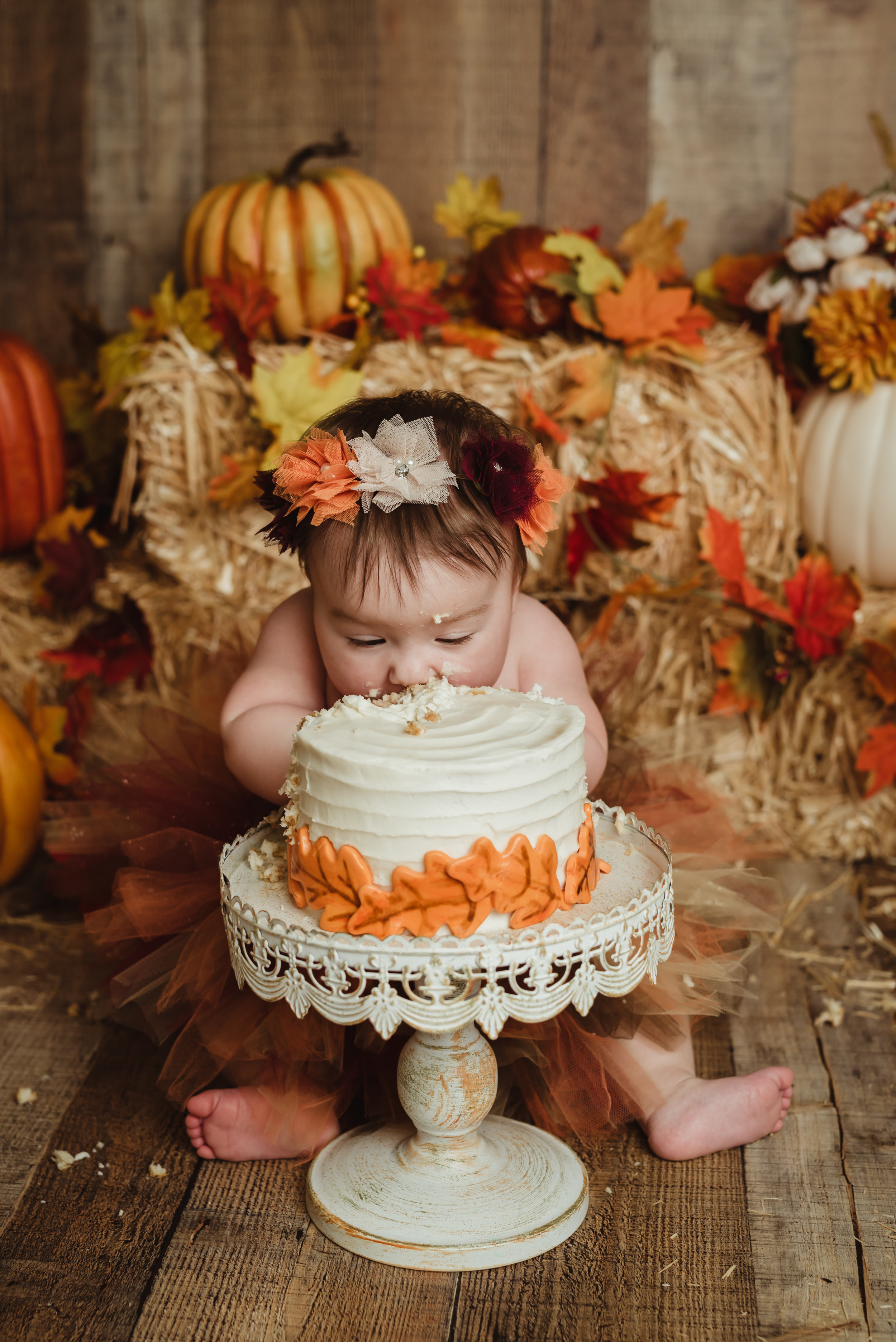 little girl with a fall theme eating her cake face first with junebug photography studio in manhattan, ks
