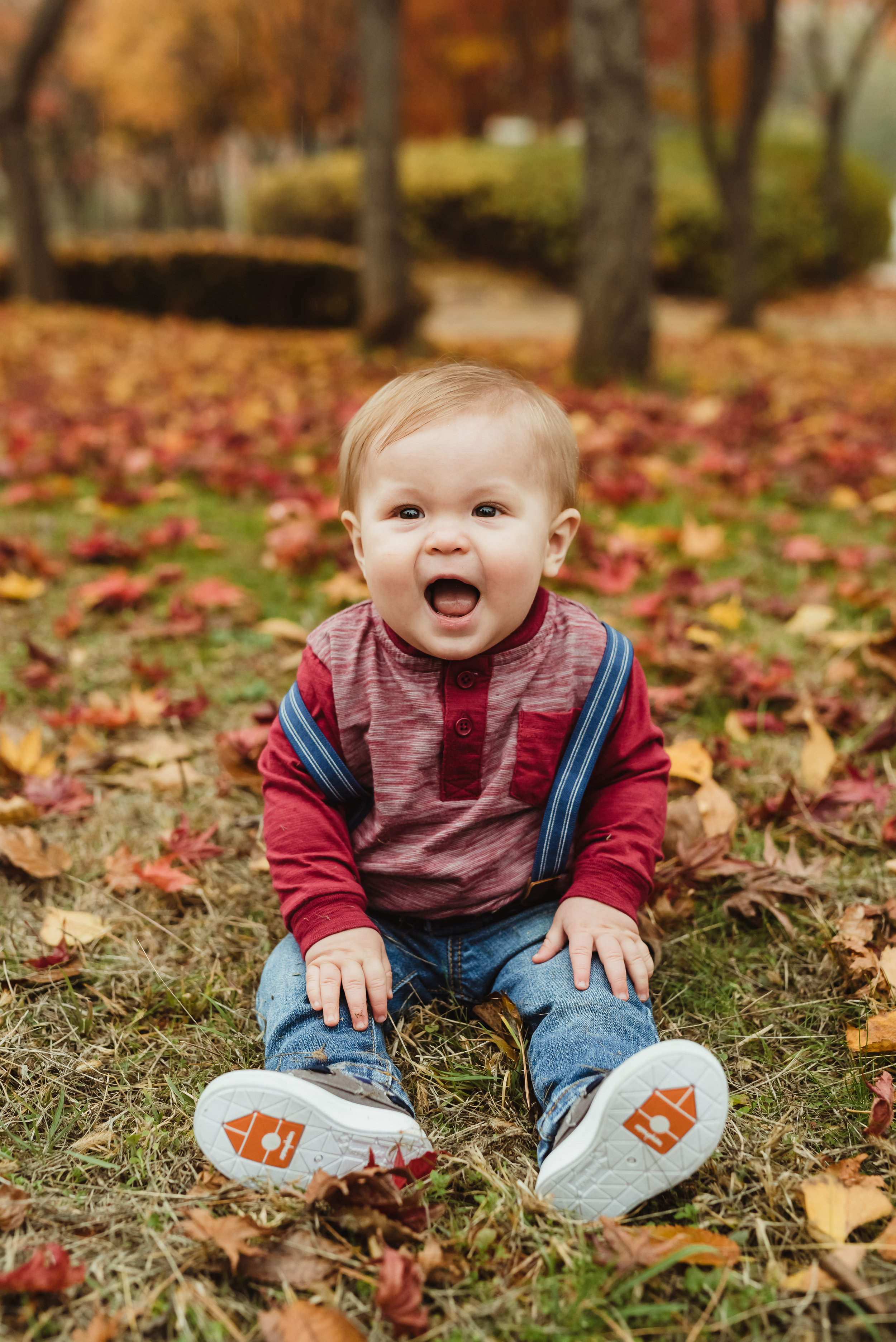 happy baby boy in some fall leaves with junebug photography studio in manhattan, ks