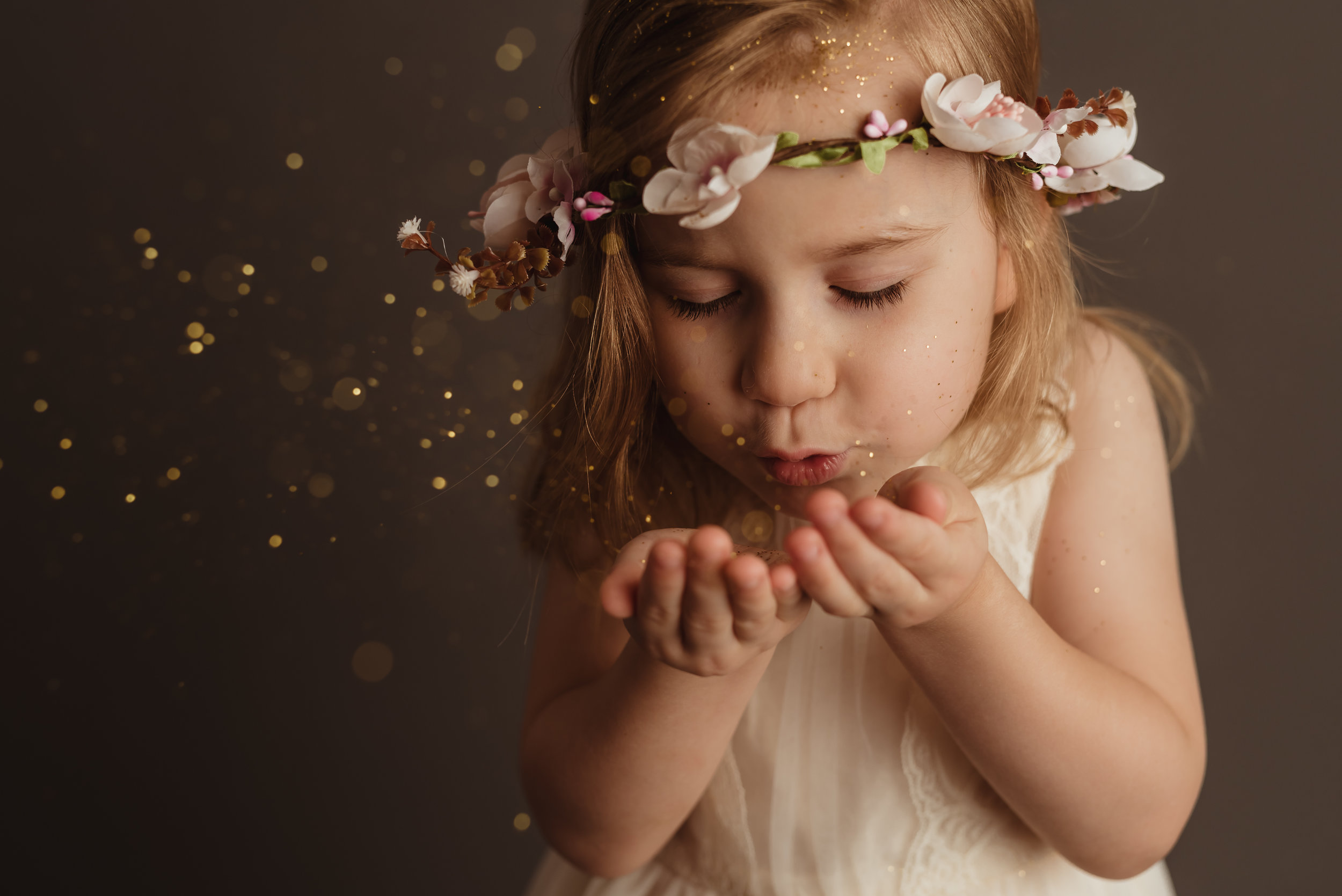 blowing glitter from her hands with junebug photography studio in manhattan, ks