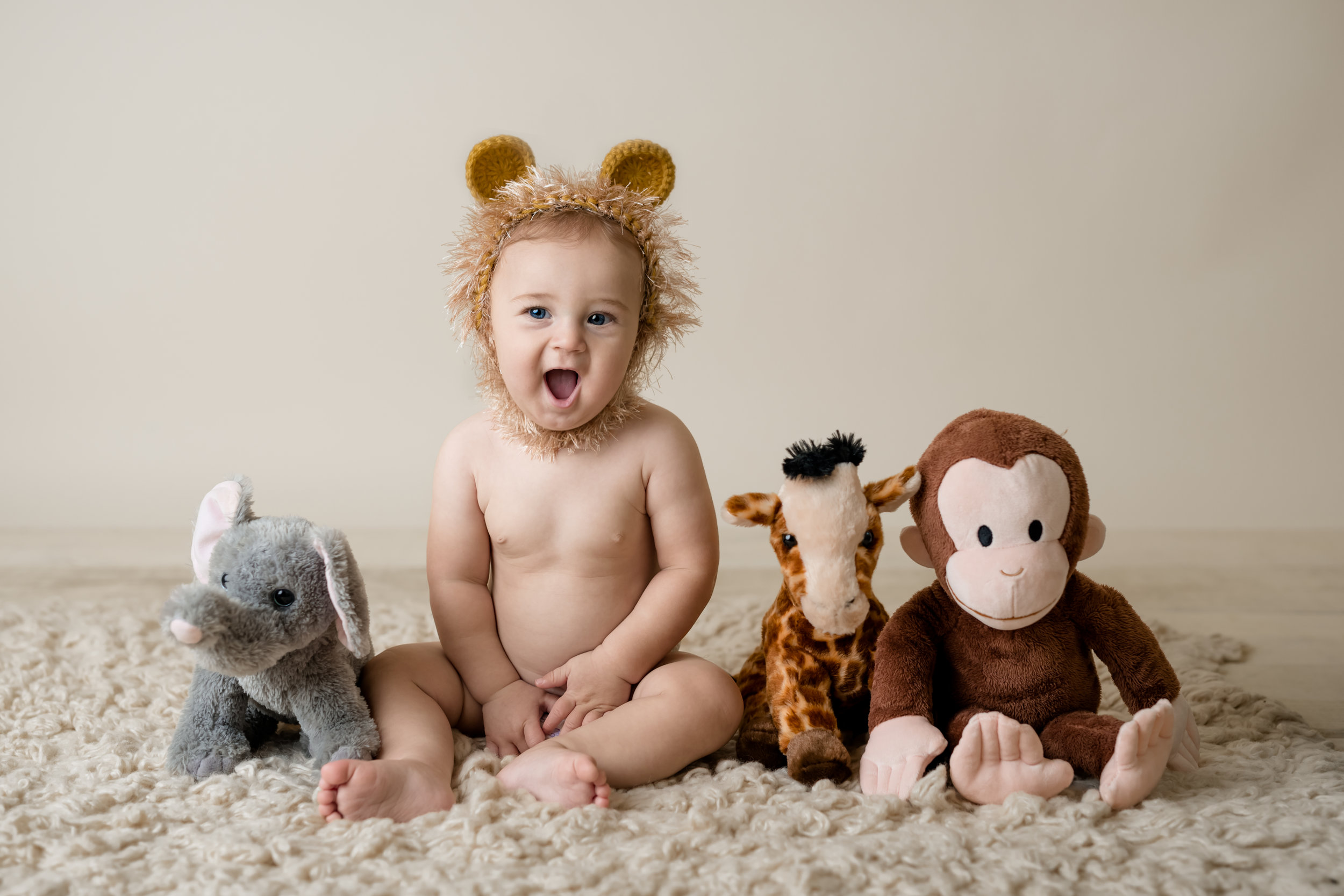 happy boy in a lion hat with the rest of his jungle animal friends with junebug photography studio in manhattan, ks