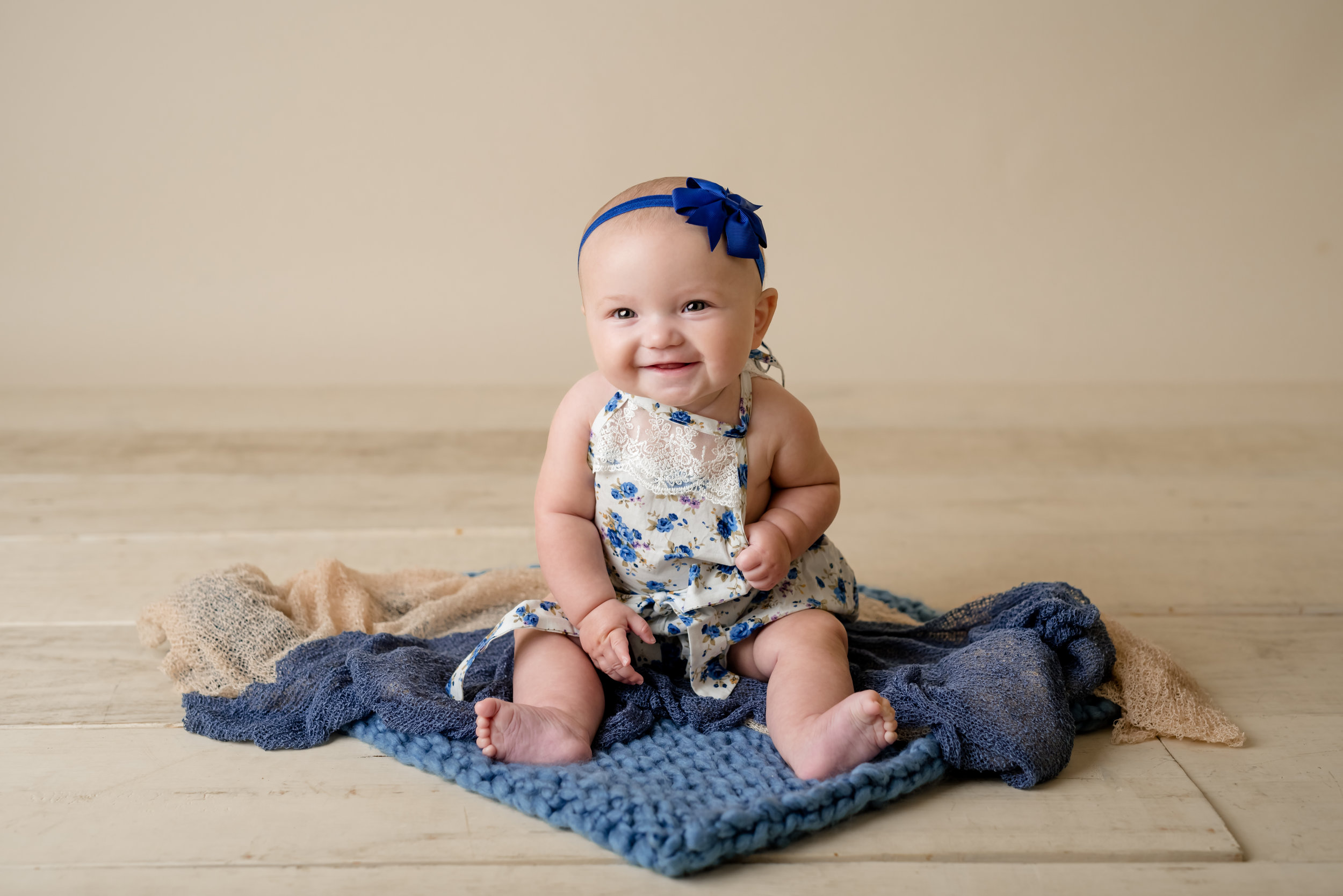 six month old baby girl in blue during a sitter session with junebug photography studio in manhattan, ks
