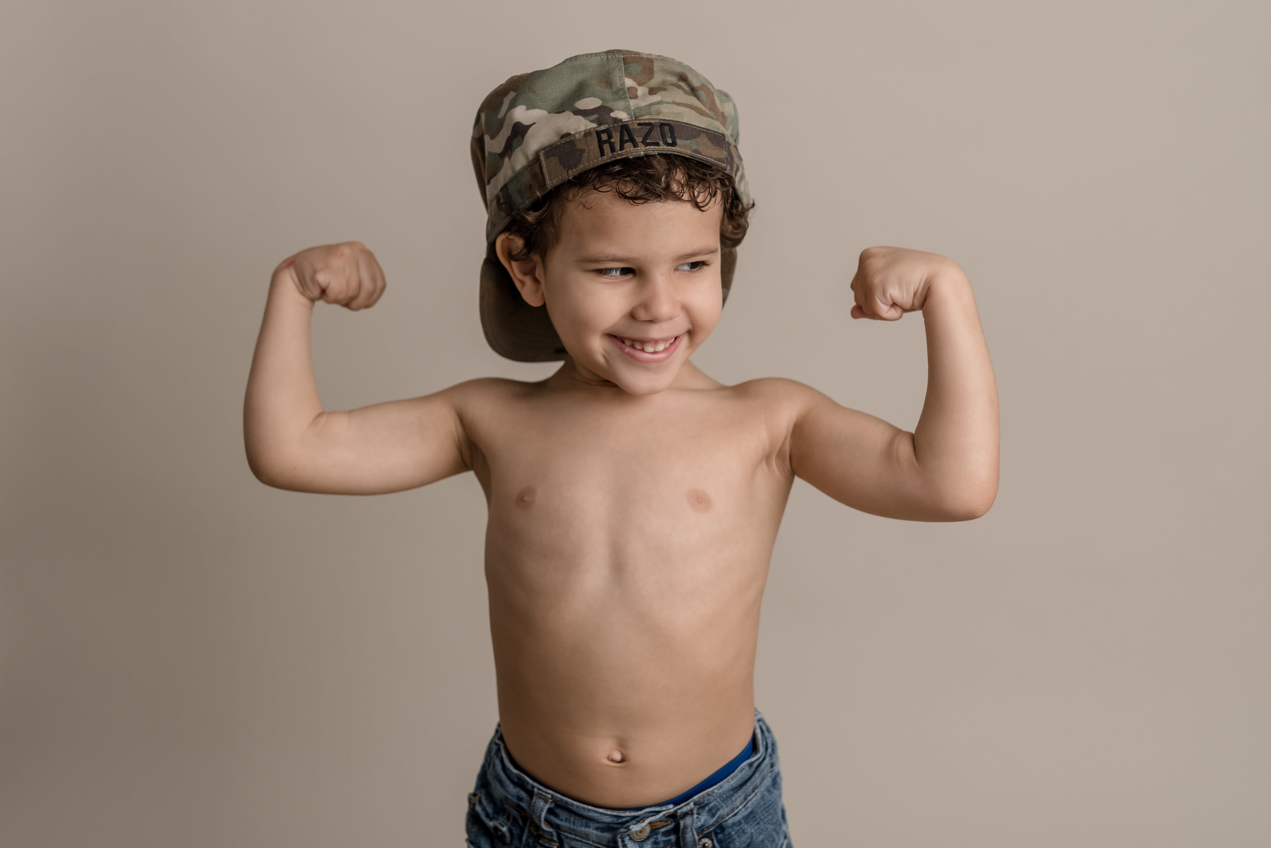 little boy showing off his muscles in his dad's army hat with junebug photography studio in manhattan, ks