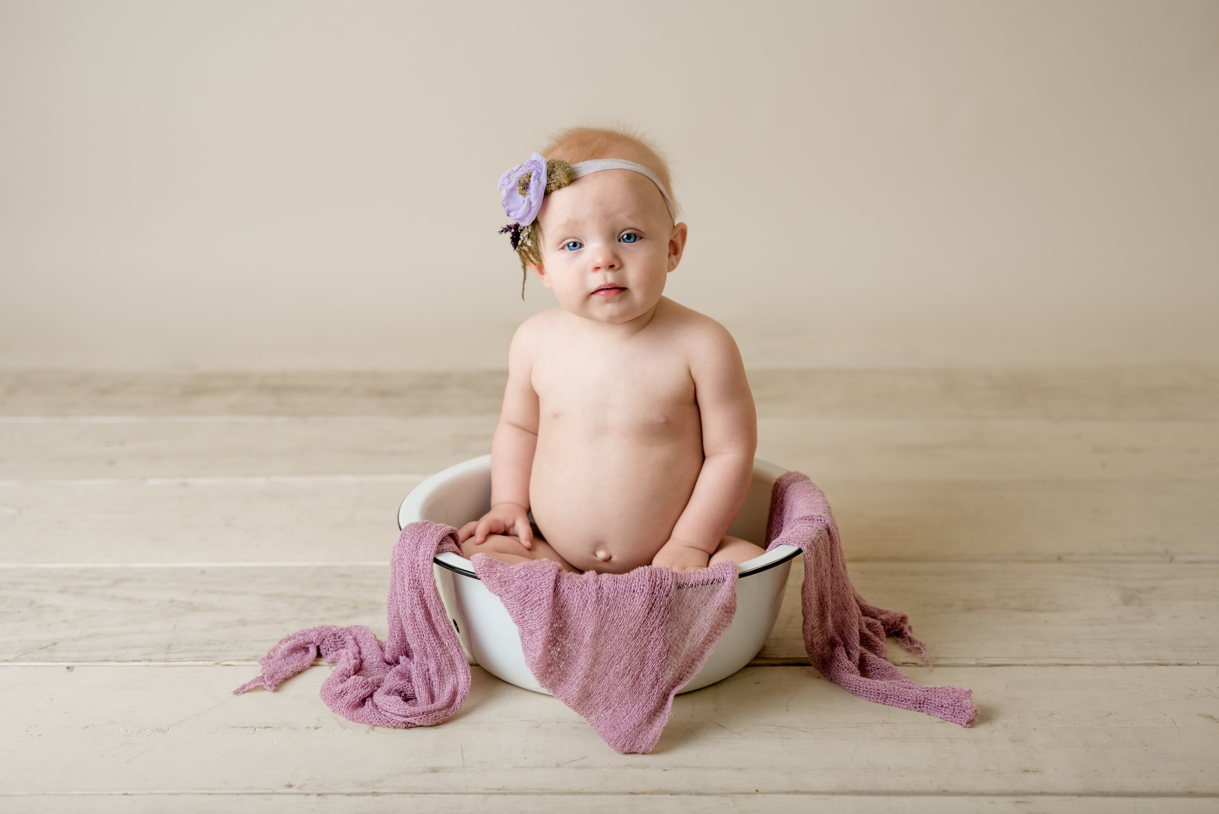 baby girl in purple during a sitter session with junebug photography studio in manhattan, ks
