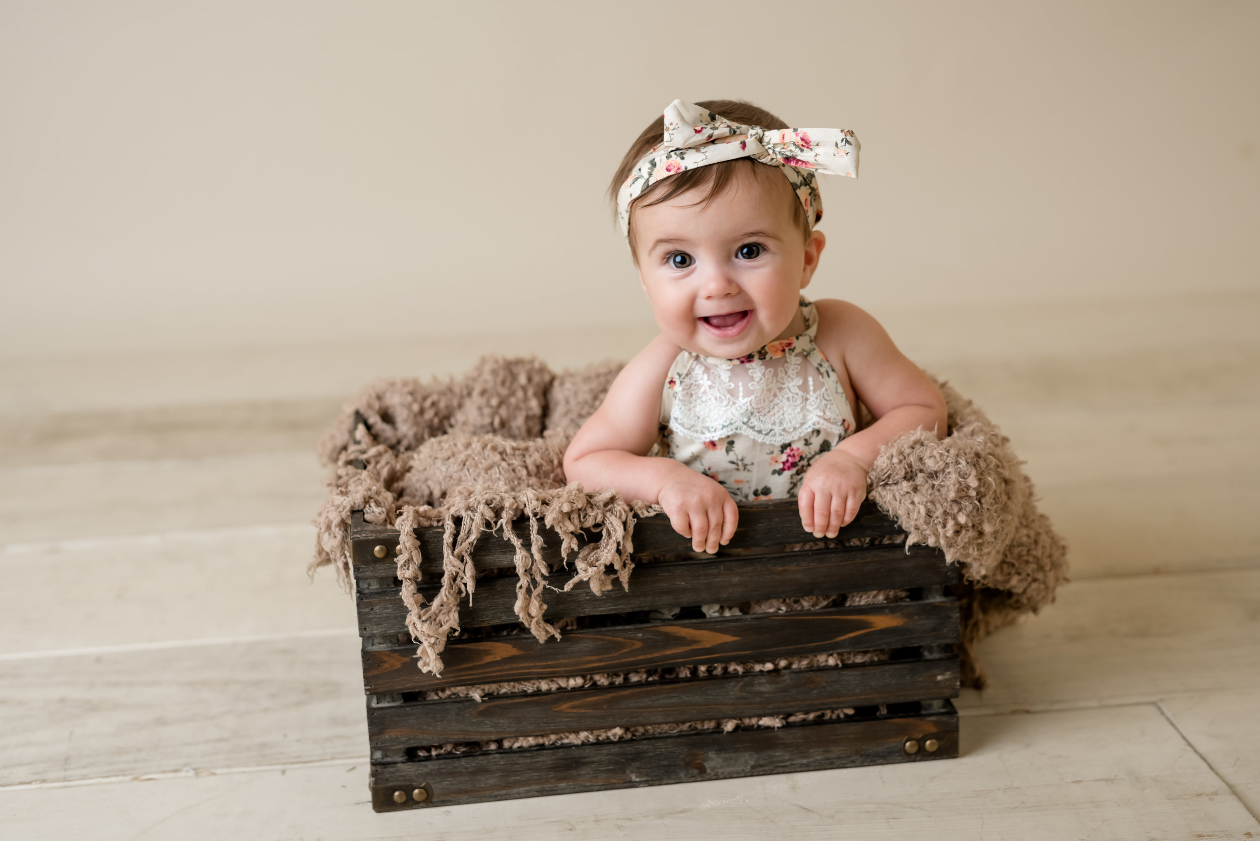 baby girl in a wooden crate with junebug photography studio in manhattan, ks