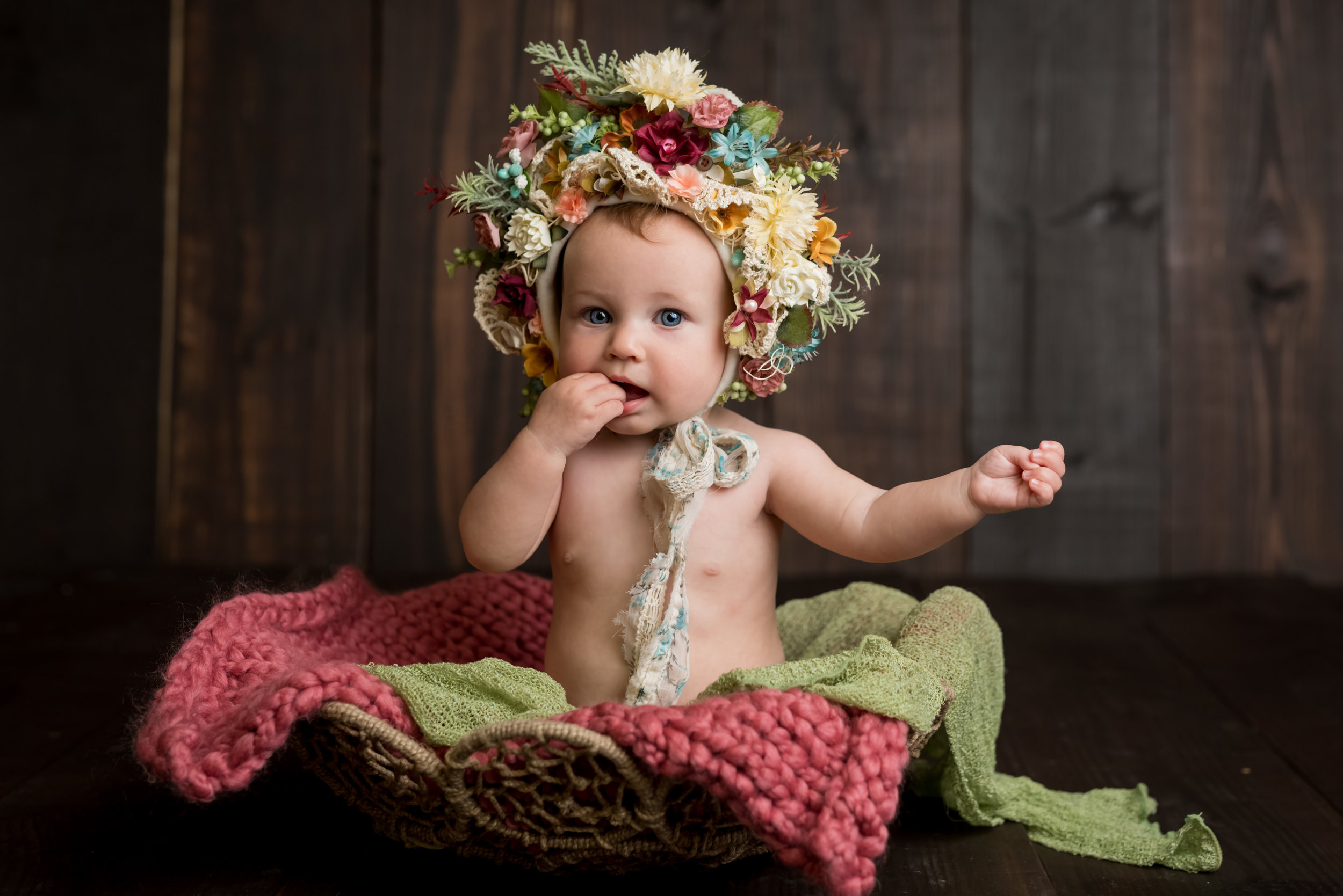 sweet girl sucking on her fingers in a floral bonnet during a sitter session with junebug photography studio in manhattan, ks