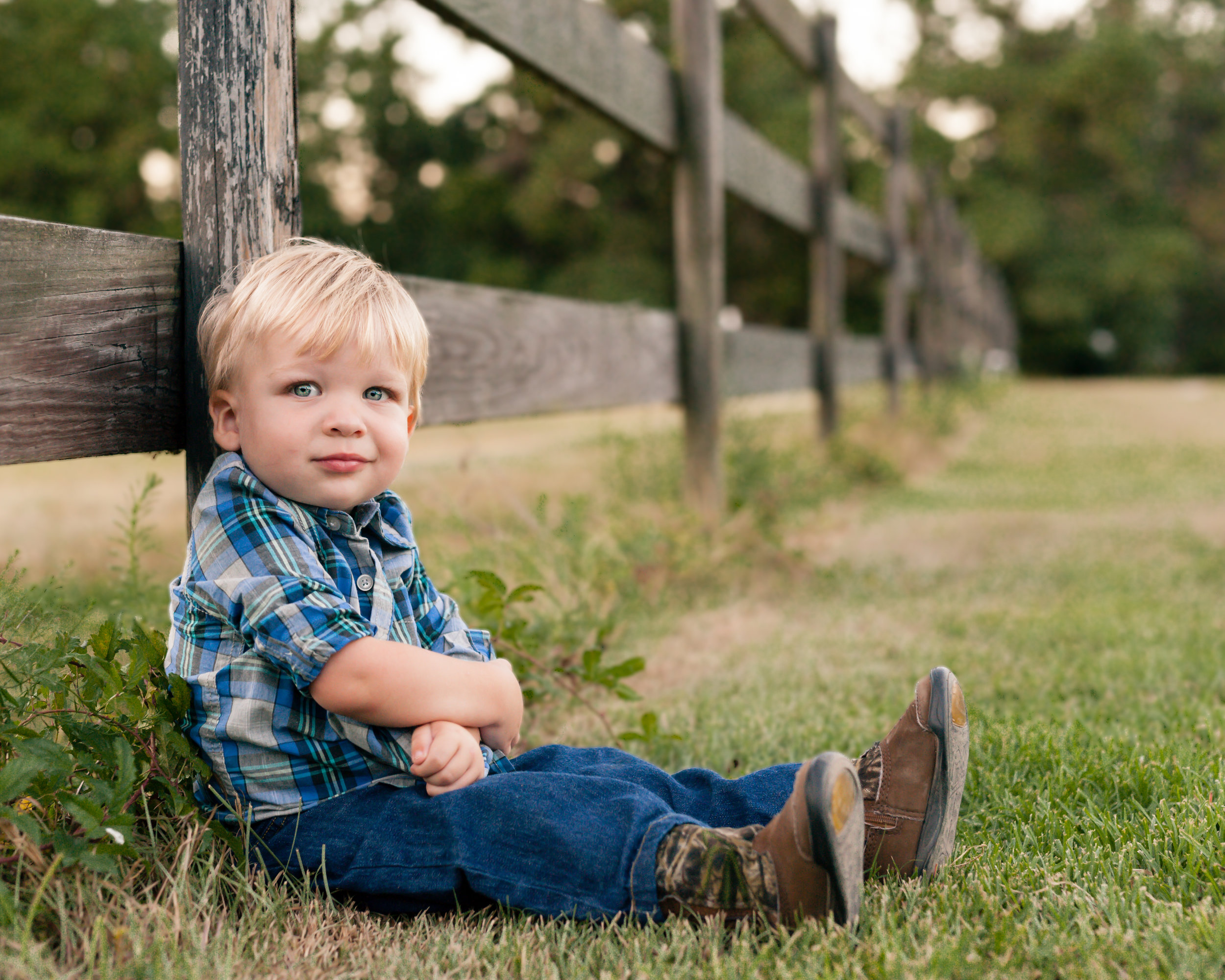 sweet boy sitting by a fence with junebug photography studio in manhattan, ks