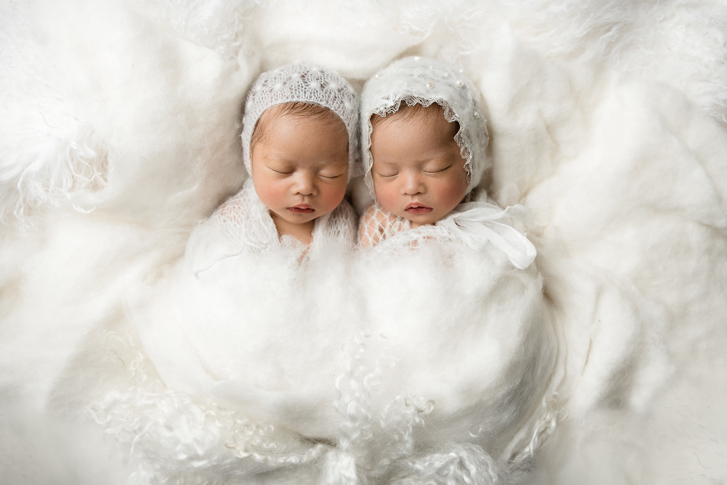 asian twins wrapped and snuggled together at junebug photography studio in manhattan, kansas