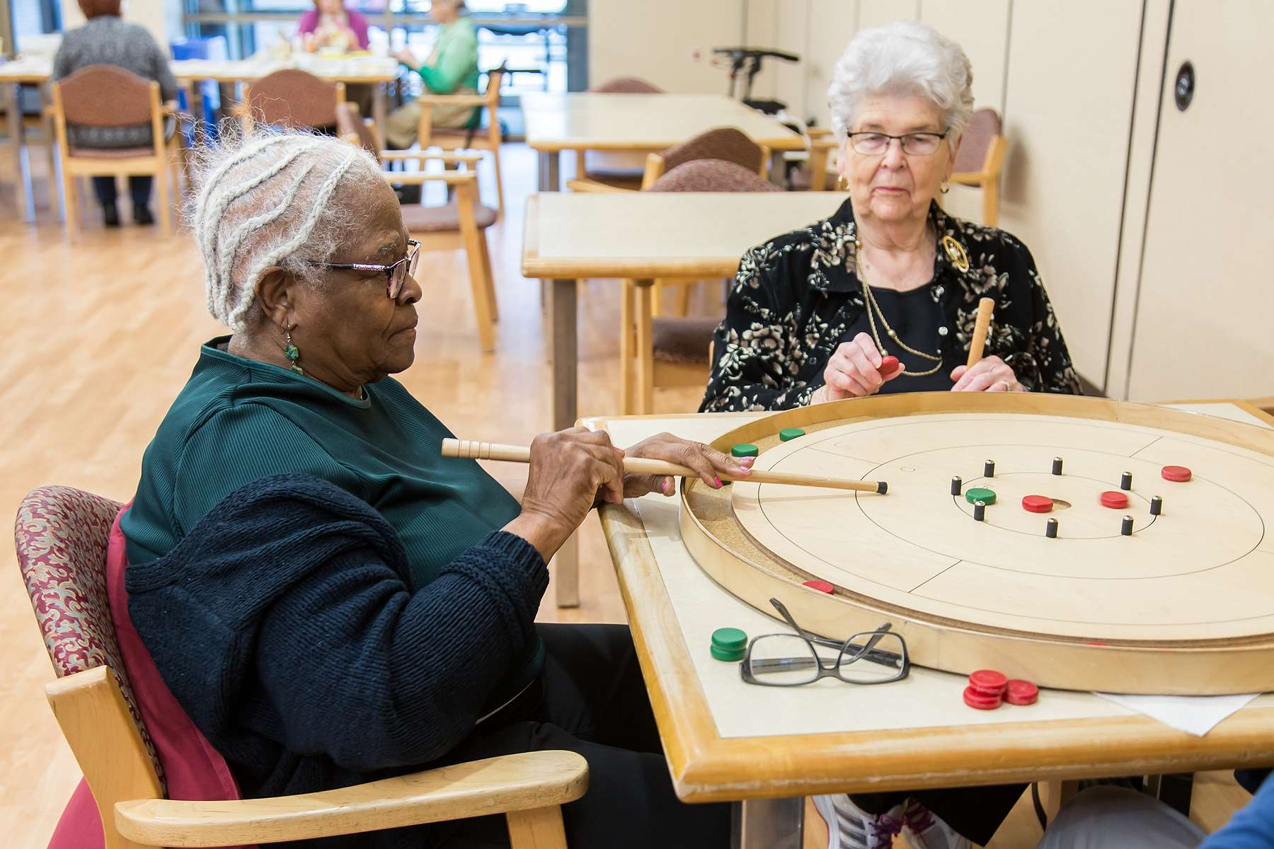 Two clients playing crokinole