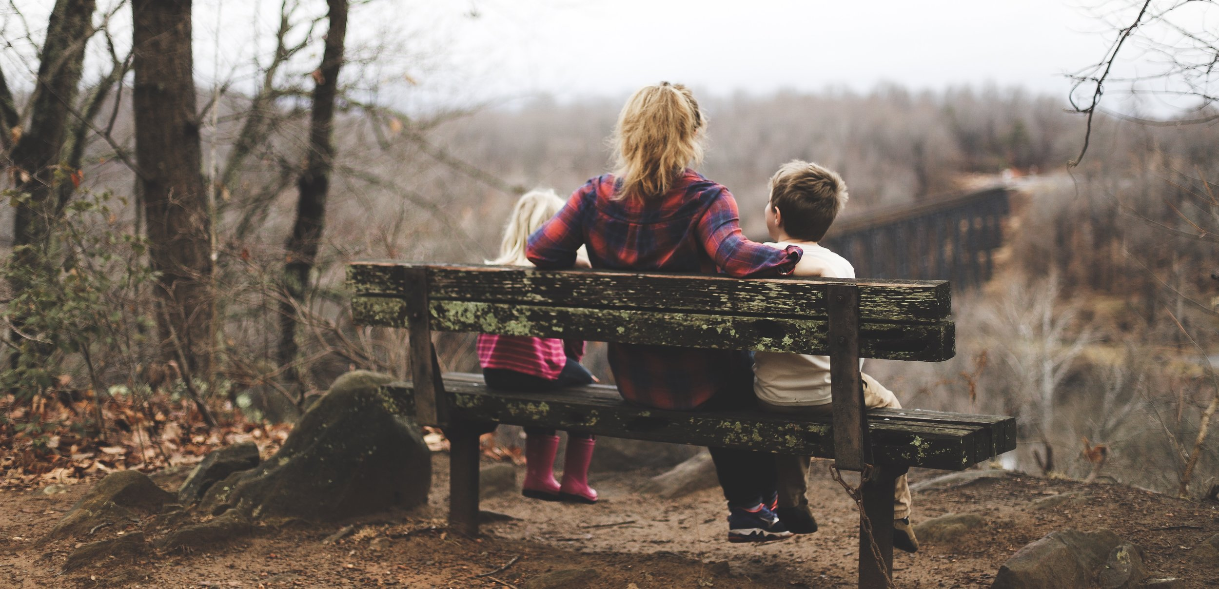 Woman on bench with children. Overcome anger and frustration with children.