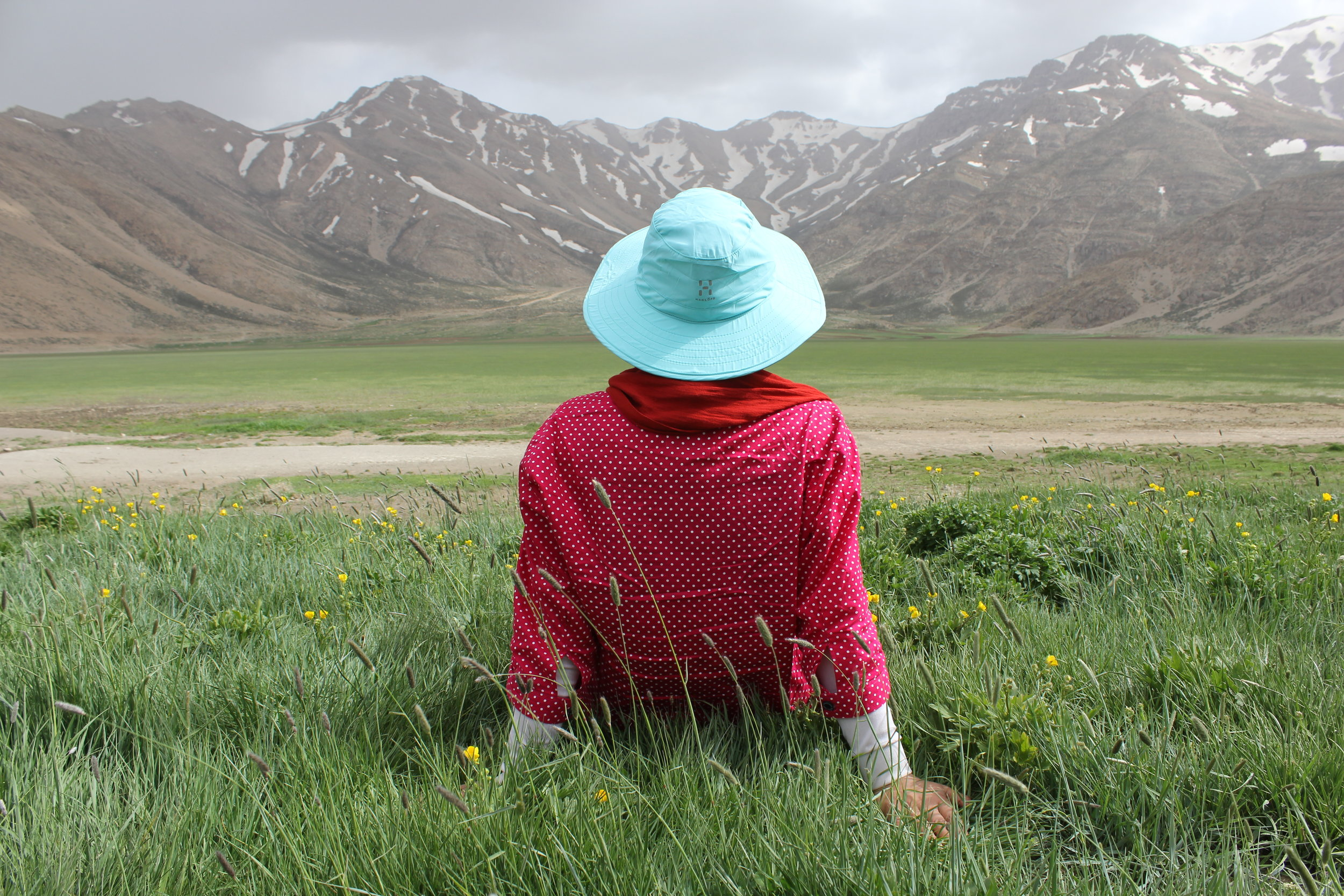 Woman enjoying view of mountains in a meadow. Free from anxiety. Tipi helps.