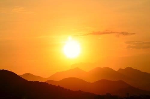 Sun setting in orange sky over mountain range