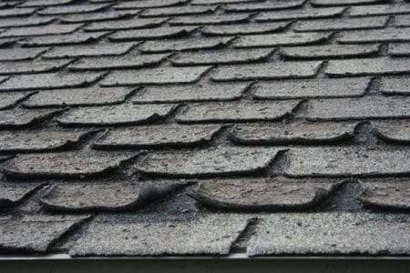 Worn out shingles curling on roof