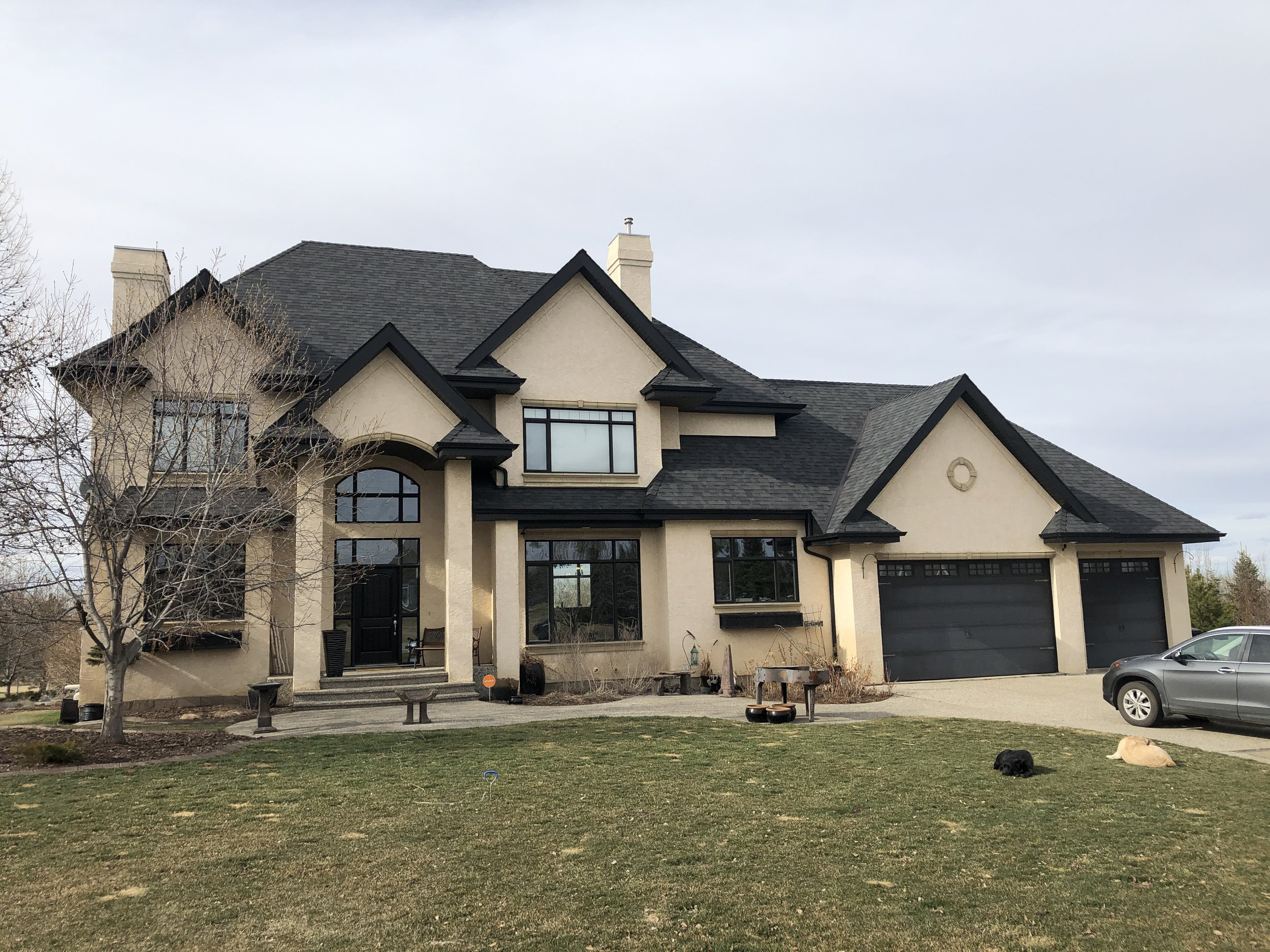 Large tan house with attached garage and midnight black shingles