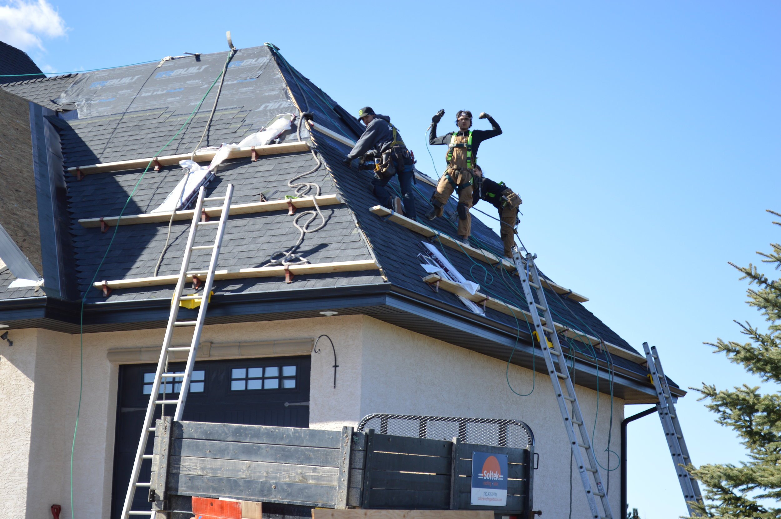 Roofers installing midnight black shingles on a tan stucco house
