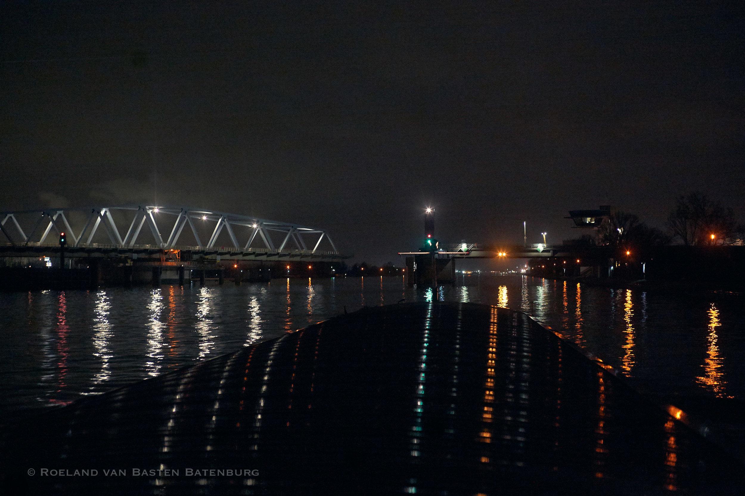 De brug bij Sluiskil. Er vaart een zeeschip achter ons dat door de brugopening zal gaan, de brug wordt al geopend. Andere schepen mogen dan niet door die opening. Voor ons geen probleem, wij nemen altijd de zij-overspanning aan stuurboord (met de dubbele gele lichten) en hoeven dus niet te wachten.
