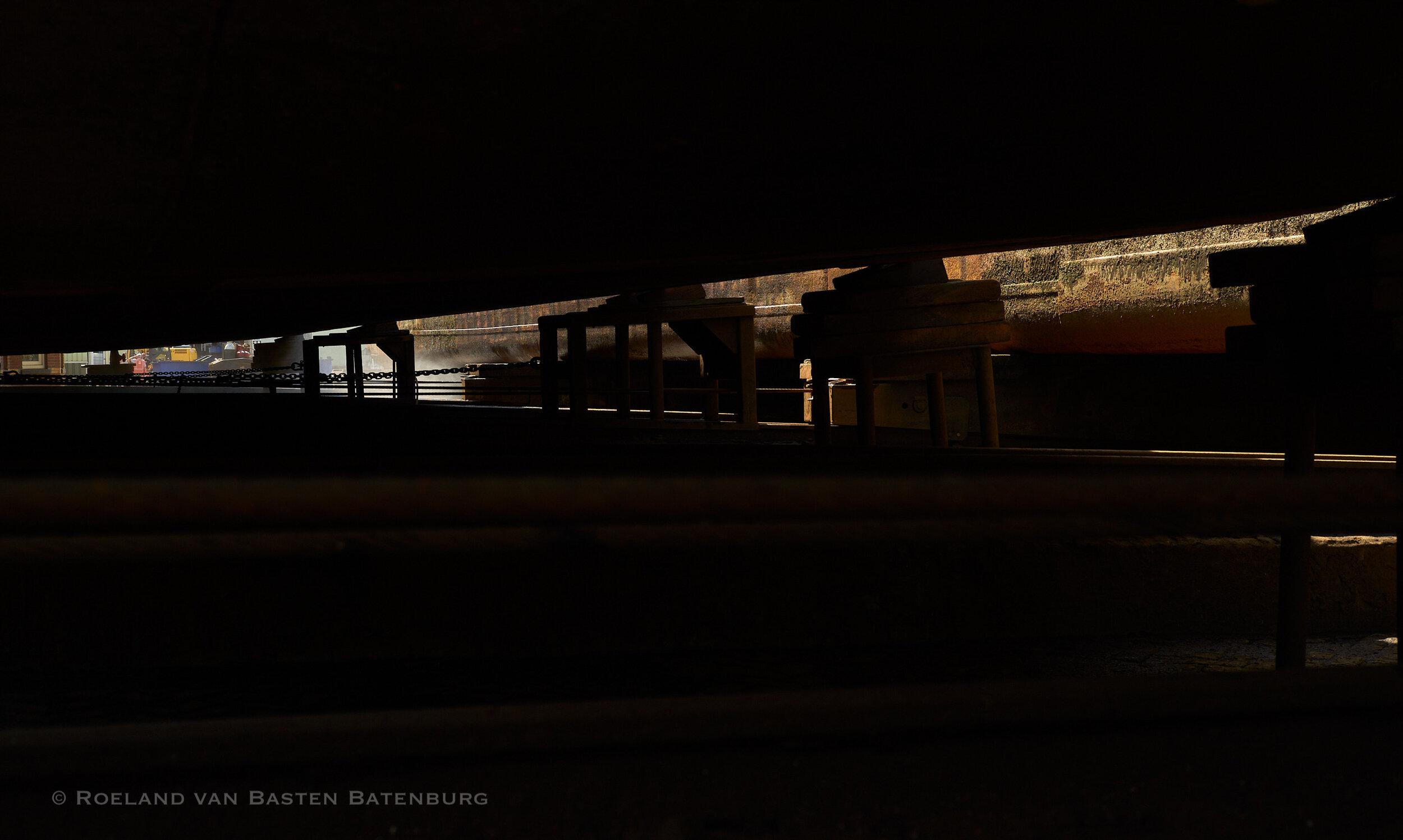 Onder het vlak van het schip door kijkend kunnen we de blokken zien waar het schip op staat en zien we het schip dat naast ons ligt