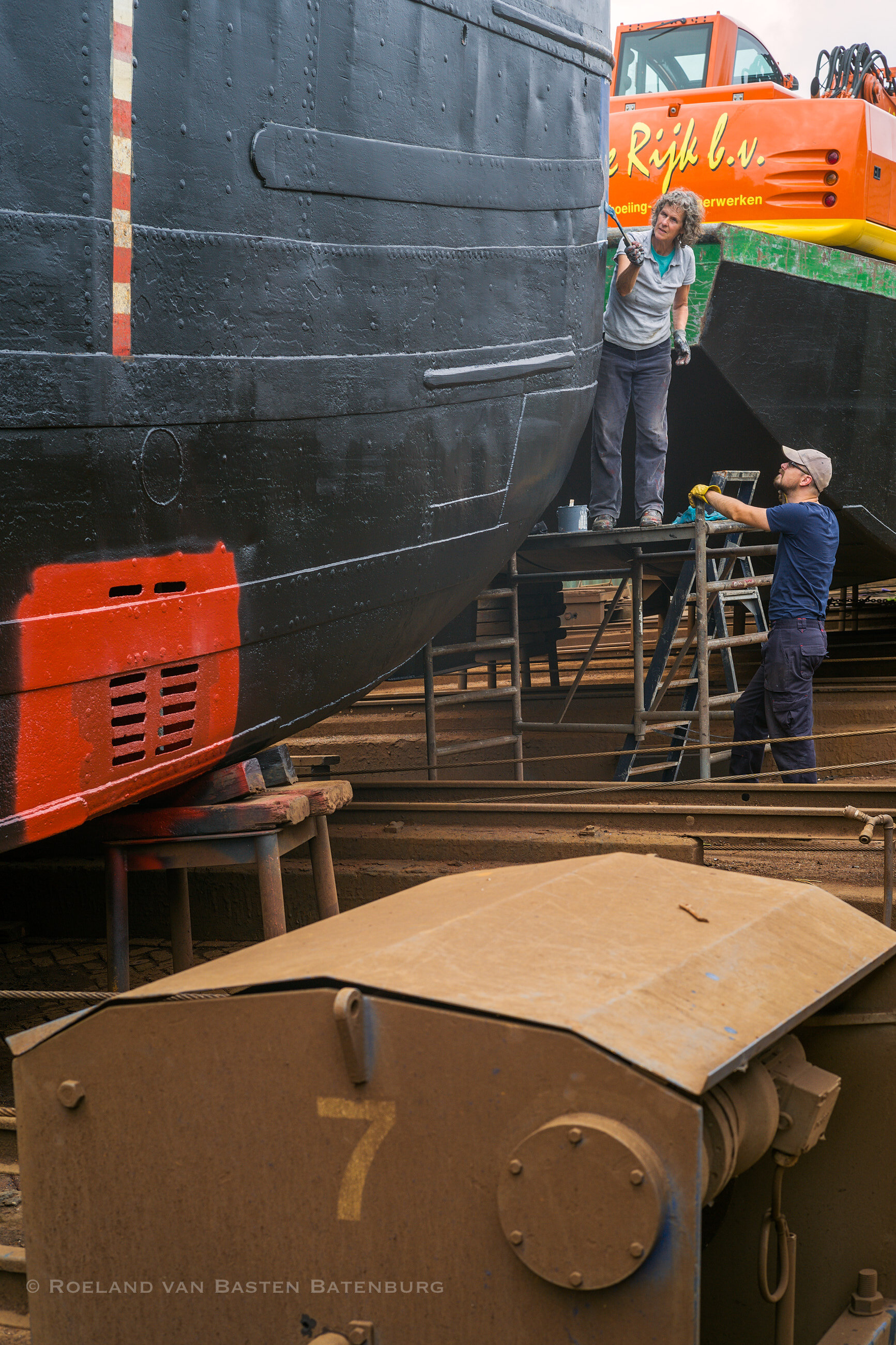 De nieuwe laag teervervanger zit er intussen op, meerdere lagen tot aan de waterlijn (met leeg schip), daarboven een enkele van weer een andere samenstelling. Degelijk vakwerk.  Het oranje-rode stuk is antifouling op de waterinlaat van de beunkoeler, die vervangen is