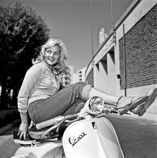 Italian actress, Virna Lisi, photographed by Pierluigi Praturlon in 1957, posing on a Vespa at the Cinecittà studios in Rome.