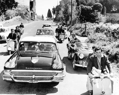 Paparazzi on Vespas and in Triumph TR3 chasing Anita Ekberg's Ford Fairlane on its way to Rome, following her arrival at the airport in Federico Fellini's most famous of films - La Dolce Vita