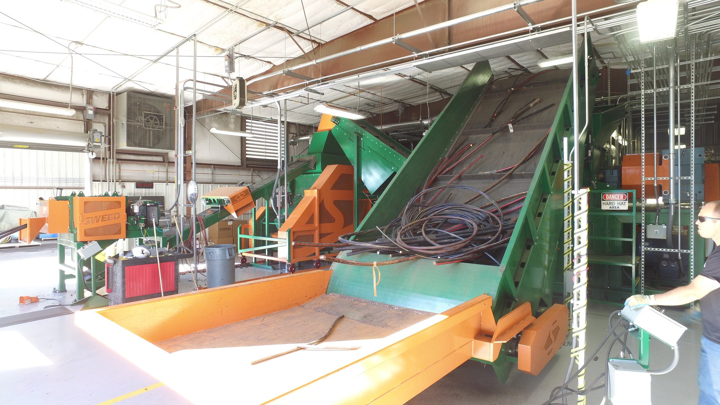 View of Sweed's 5703 XHD scrap chopper (left background) dereeling URD cable and bulk cable traveling on conveyor to shredder.